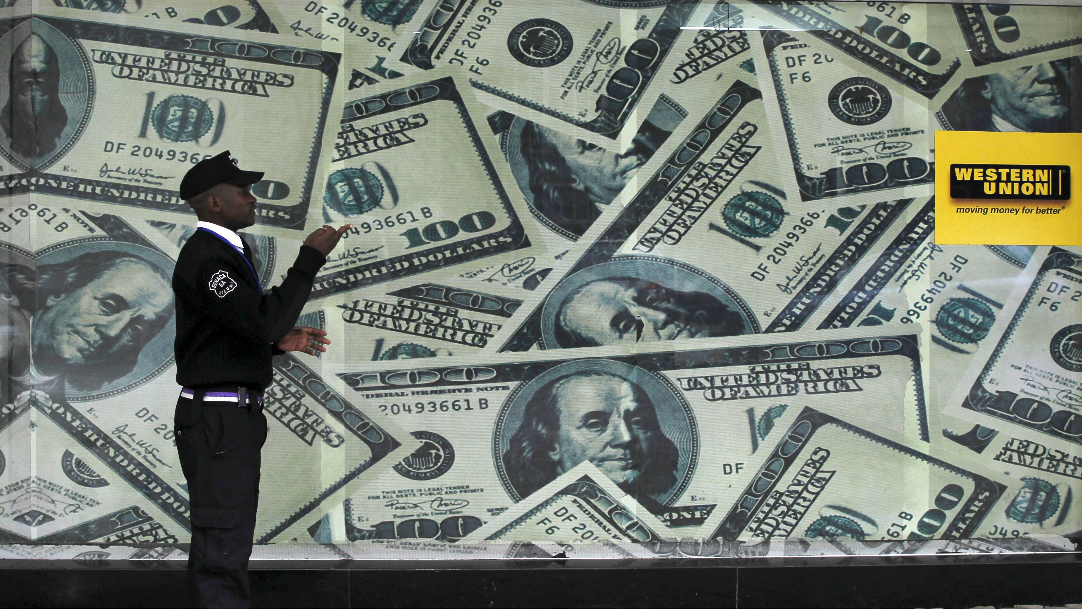 A security passing by a wall of money.