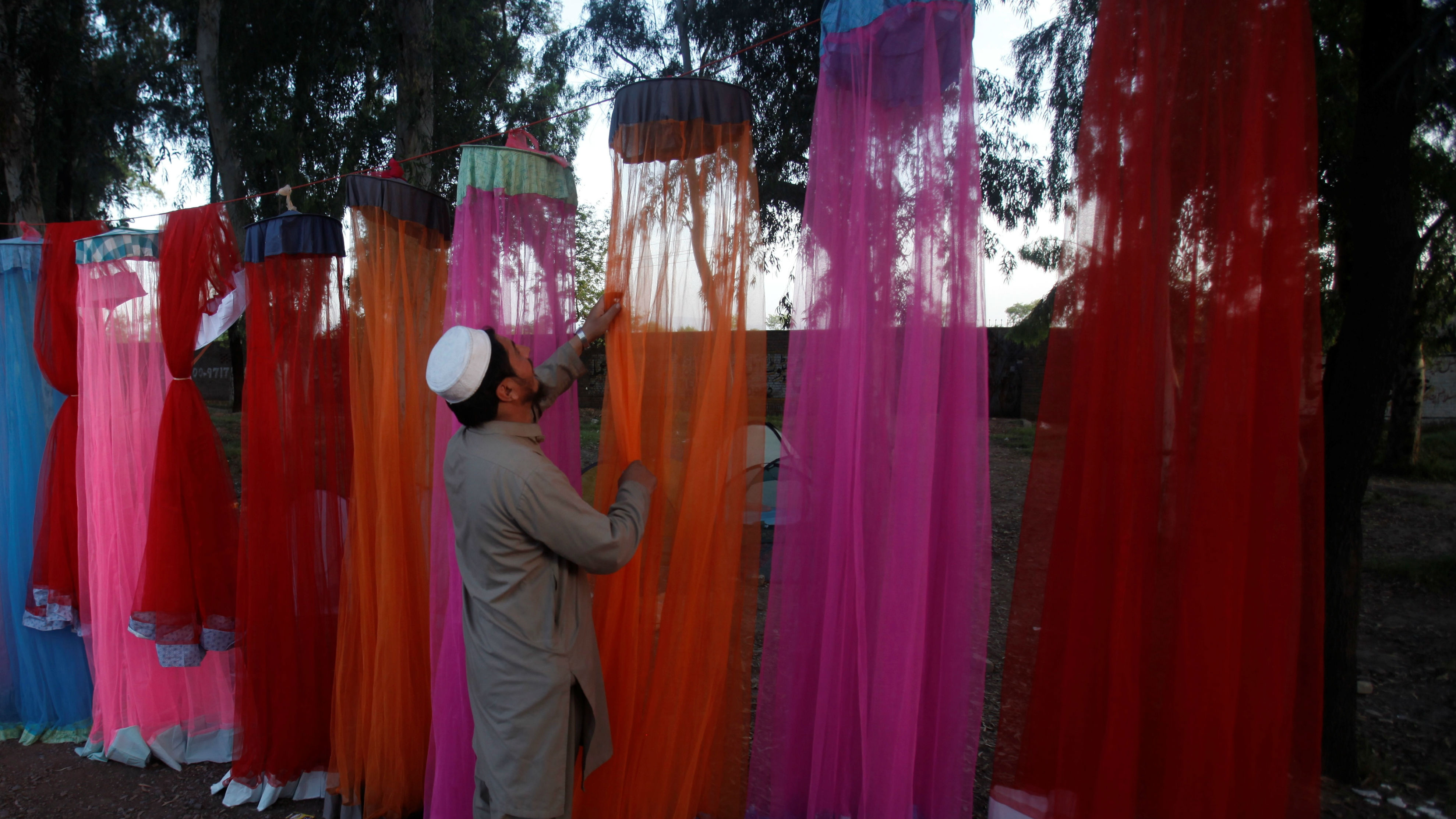 A vendor checks his stock of mosquito nets at a roadside stall in Nowshera, Pakistan