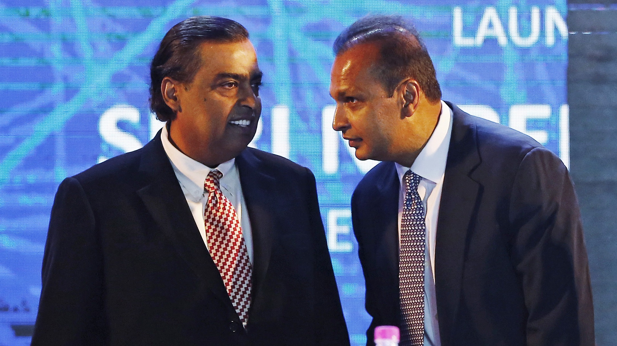 """Anil Ambani (R), chairman of the Reliance Anil Dhirubhai Ambani Group, talks to his brother Mukesh Ambani, chairman of Reliance Industries Limited, during the launch of ìDigital India Weekî in New Delhi, India, July 1, 2015. Prime Minister Narendra Modi urged more companies to make electronic and digital goods on Wednesday, reviving his campaign promise to bridge India's digital divide backed by over $70 billion in investment pledges. Launching a """"Digital India Week"""" aimed at popularising the government's push to connect 250,000 villages by 2019, Modi spoke of the need to boost local manufacturing of electronics - the country's largest import after oil. REUTERS/Adnan Abidi - RTX1IMF2"""