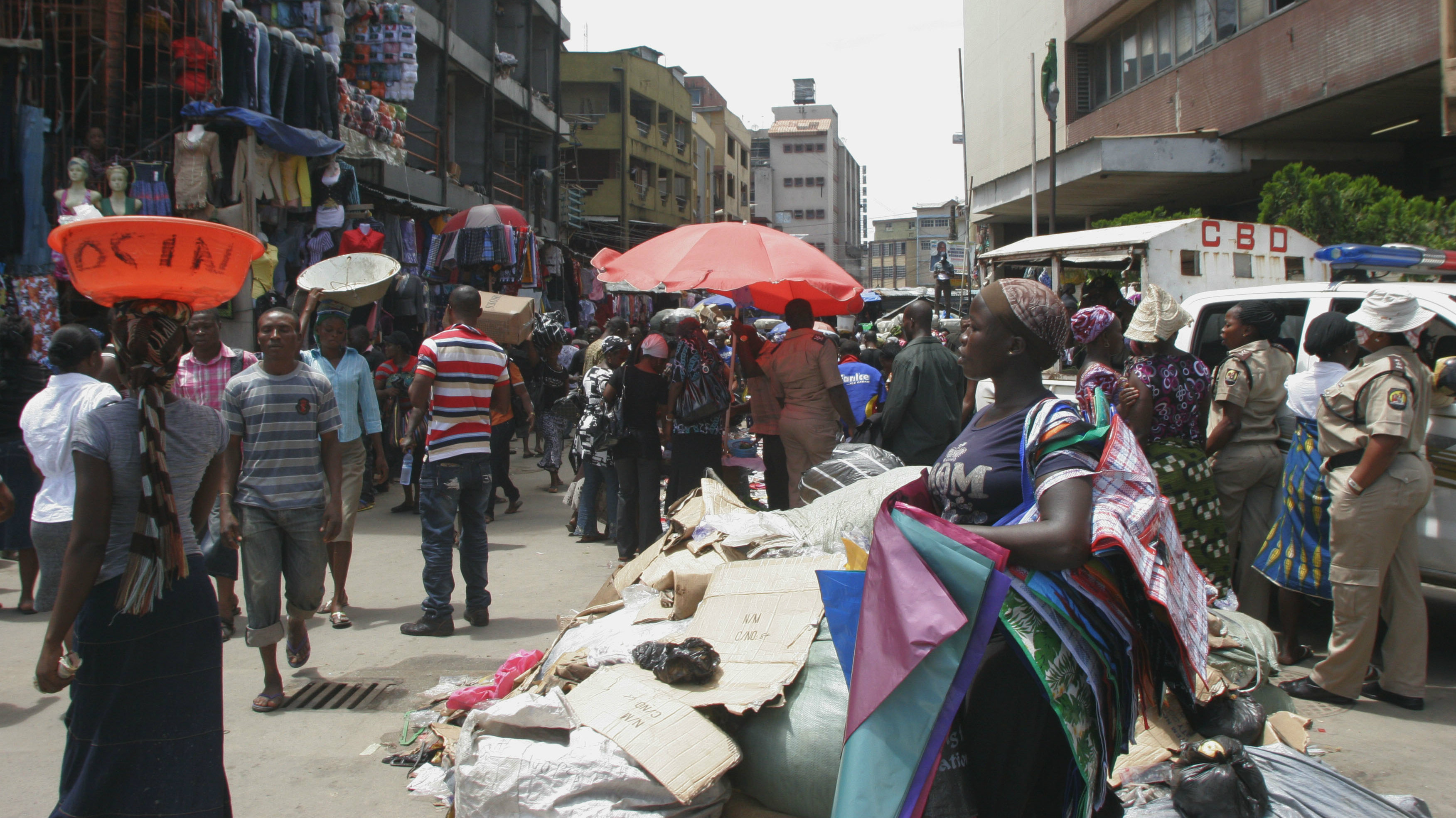 In this Thursday, Oct. 11, 2011 photo, a woman woman sells plastic bags in a busy market on Lagos Island in Lagos, Nigeria. Lagos is expected to overtake Cairo soon as Africa's largest city. In Nigeria's commercial capital, the population is estimated at 15 million and growing at 6 percent or more each year. Problems with traffic congestion, sanitation and water supplies are staggering; a recent article in UN-Habitat said two-thirds of the residents live in poverty.