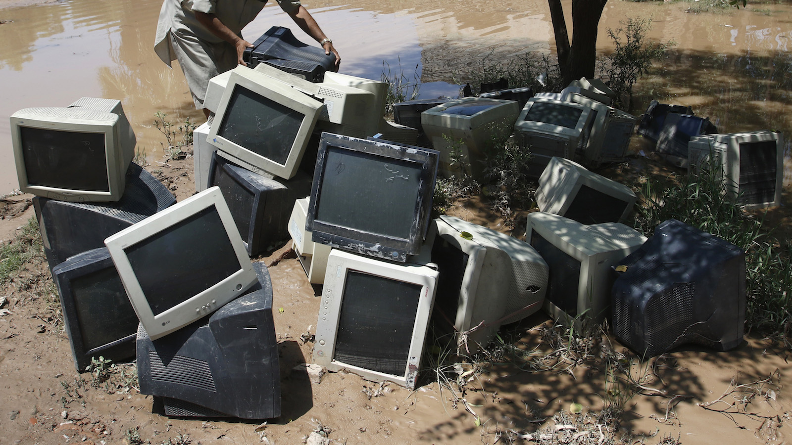 A worker moves old computer monitors after heavy rainfall caused flooding in Peshawar, Pakistan, July 27, 2015. Flash flooding caused by torrential monsoon rains has killed at least 28 in Pakistan and affected hundreds of thousands of people, according to aid agencies, with further downpours expected in the coming days. REUTERS/ Khuram Parvez - RTX1LY9Q