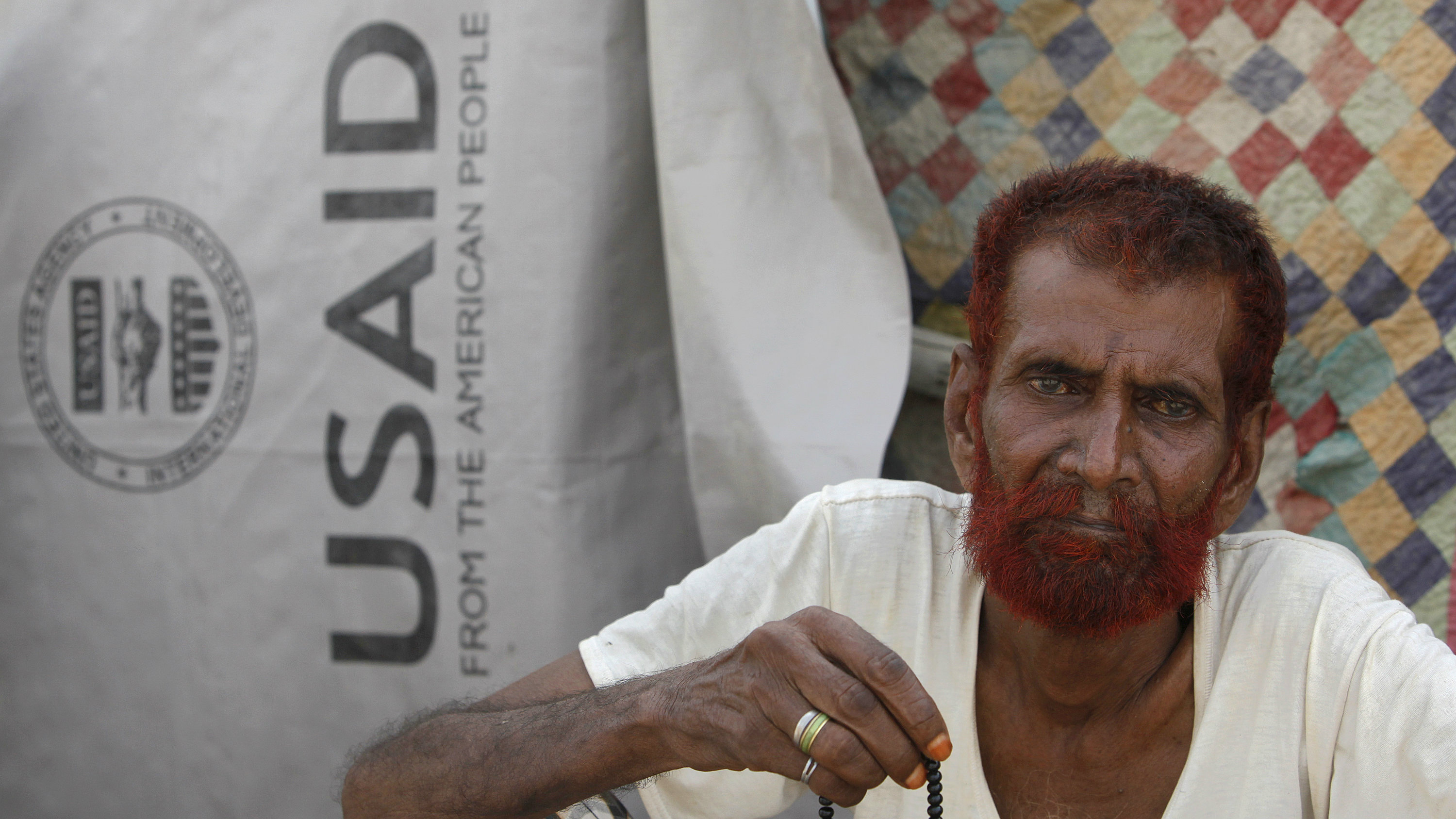 Flood victim Haji Usman holds praying beads as he sits outside his makeshift tent covered by weather sheet donated by USAID while taking refuge on an embankment at Chandan Mori village in Dadu, some 320 kilometres (199 miles) north of Karachi September 14, 2010. REUTERS/Akhtar Soomro (PAKISTAN - Tags: DISASTER ENVIRONMENT)