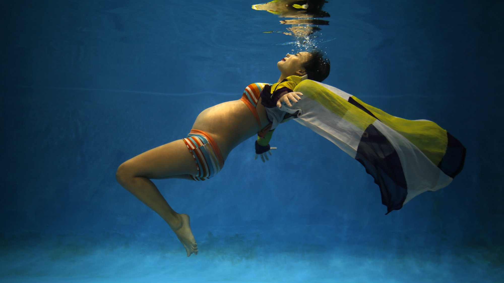 Jiejin Qiu, who is six months pregnant with her first baby, poses underwater during a photo shoot at a local wedding photo studio in Shanghai September 5, 2014.