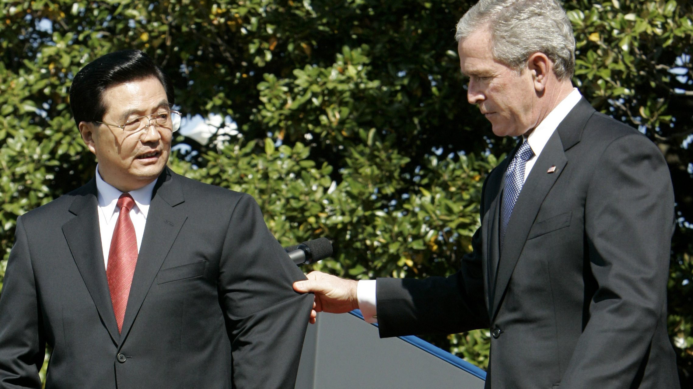 Chinese President Hu Jintao (L) looks back at U.S. President George W. Bush as Bush reaches out and pulls him back by his suit jacket as the President of China prepared to walk down the wrong set of steps to leave the stage during official South Lawn Arrival Ceremonies at the White House in Washington, April 20, 2006.      REUTERS/Jim Bourg - RTR1CMRK
