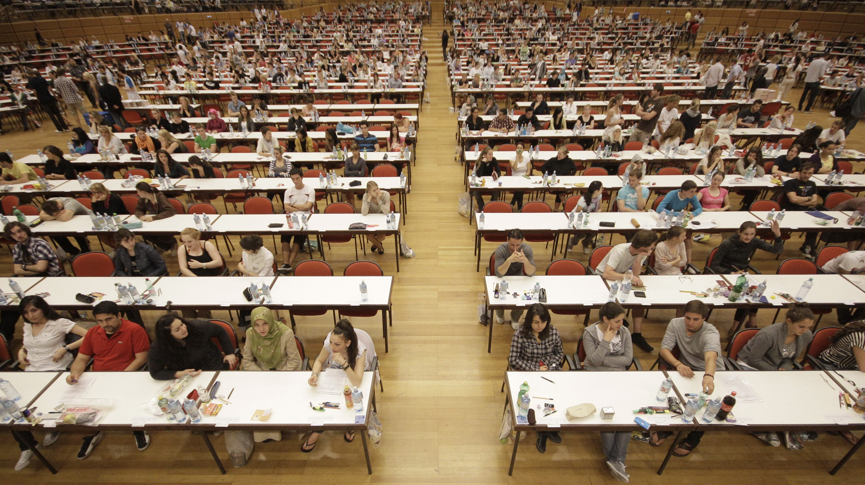 Applicants to study medicine at Vienna University wait for their qualifying examination to begin at the Austria Center convention centre in Vienna July 9, 2010. Some 4,425 people took part in the seven hour test procedure with a one-hour break, answering 198 multiple choice questions, to qualify for one of 740 places. REUTERS/Lisi Niesner  (AUSTRIA - Tags: EDUCATION IMAGES OF THE DAY) - RTR2G92P