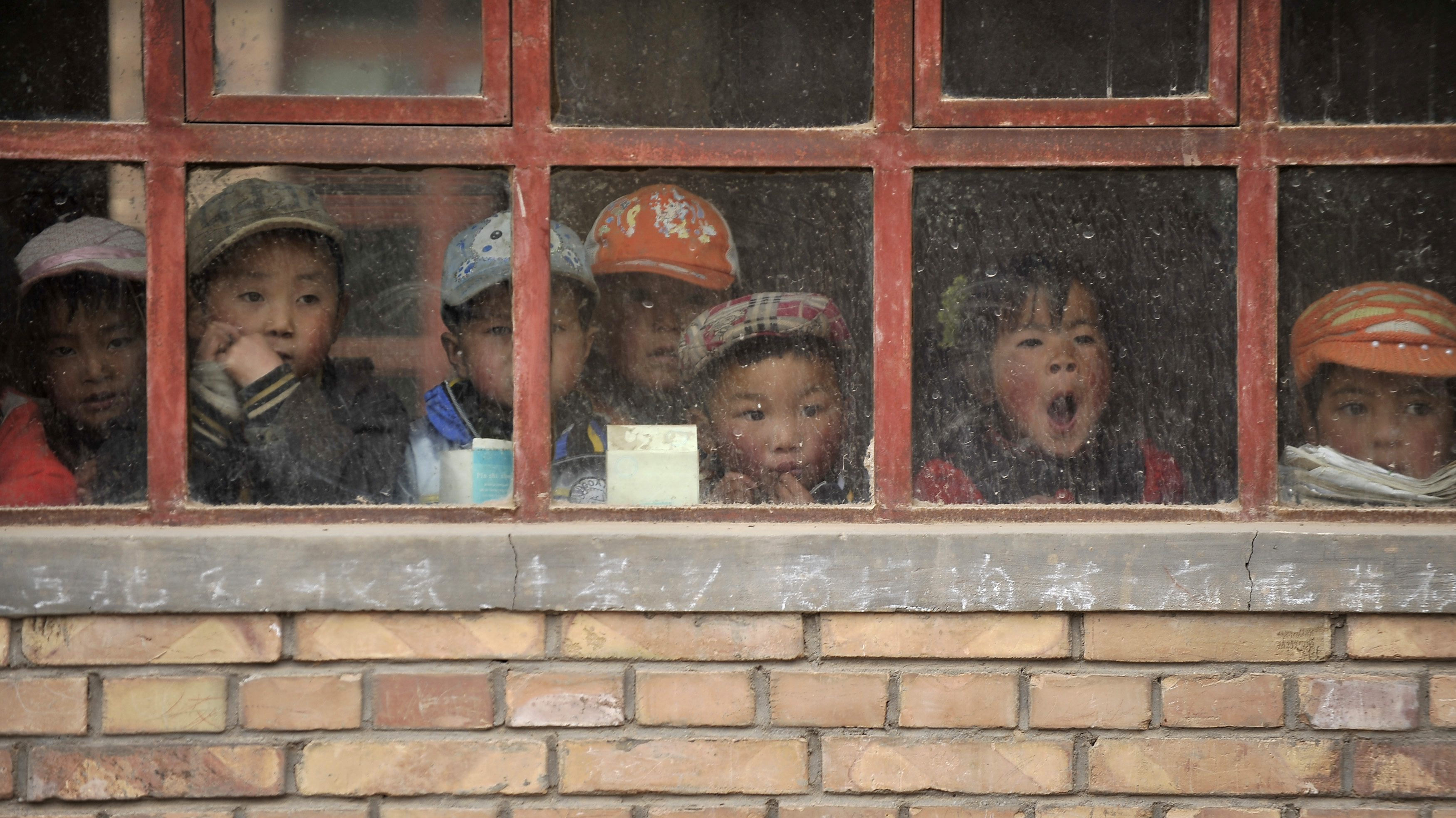 Children look out from a window of their classroom at a rural primary school in Min county, Gansu province June 1, 2011. The school, consisting of five teachers and 102 students, is located on a mountain measuring more than 2,000 meters (6,562 ft) high. REUTERS/Stringer (CHINA - Tags: EDUCATION SOCIETY) - RTR2N5JT