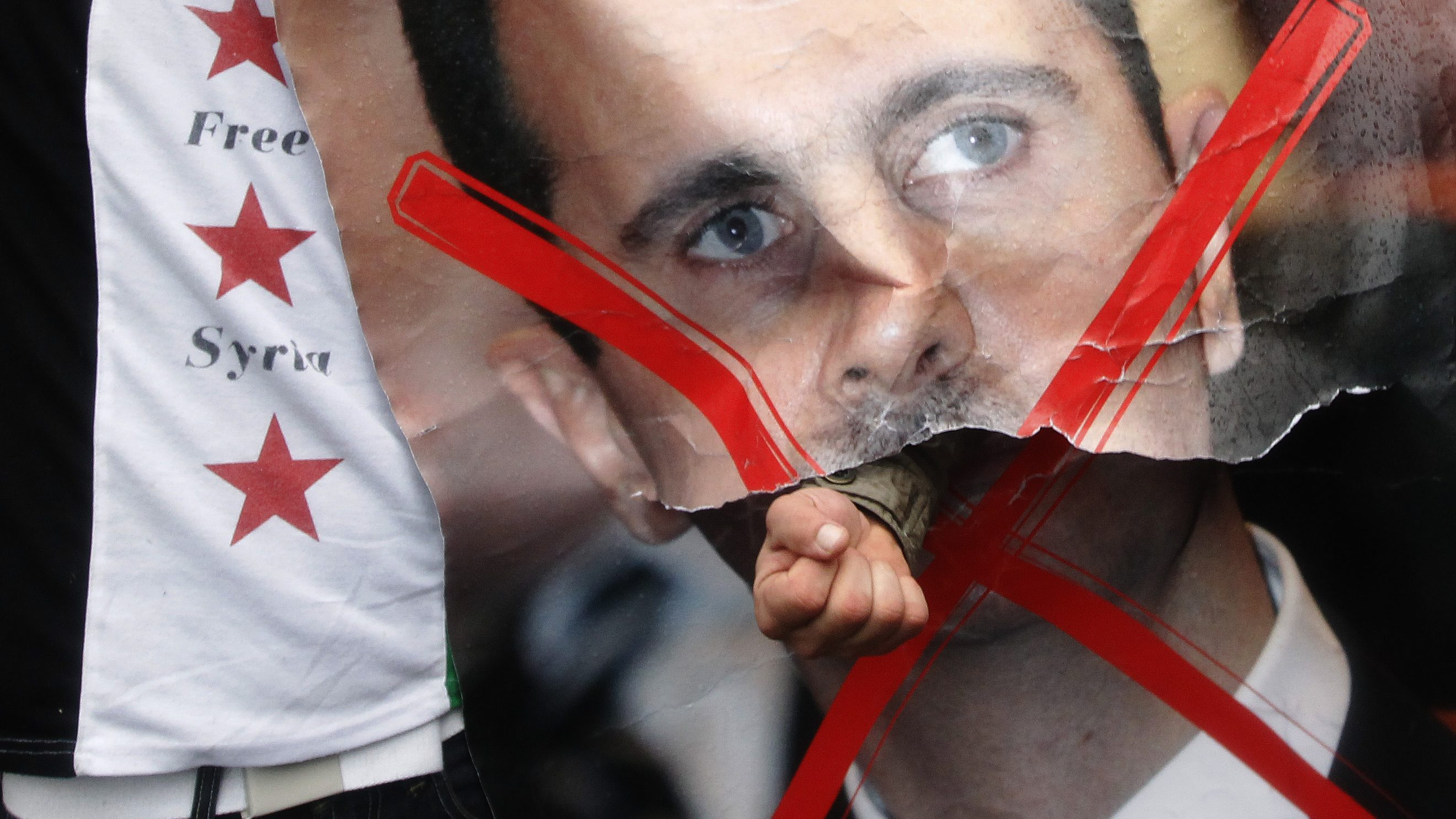 A demonstrator punches through a portrait of Syria's President Bashar al-Assad during a protest outside the Syrian Embassy in London February 18, 2012.  REUTERS/Luke MacGregor  (BRITAIN - Tags: CIVIL UNREST POLITICS) - RTR2Y289