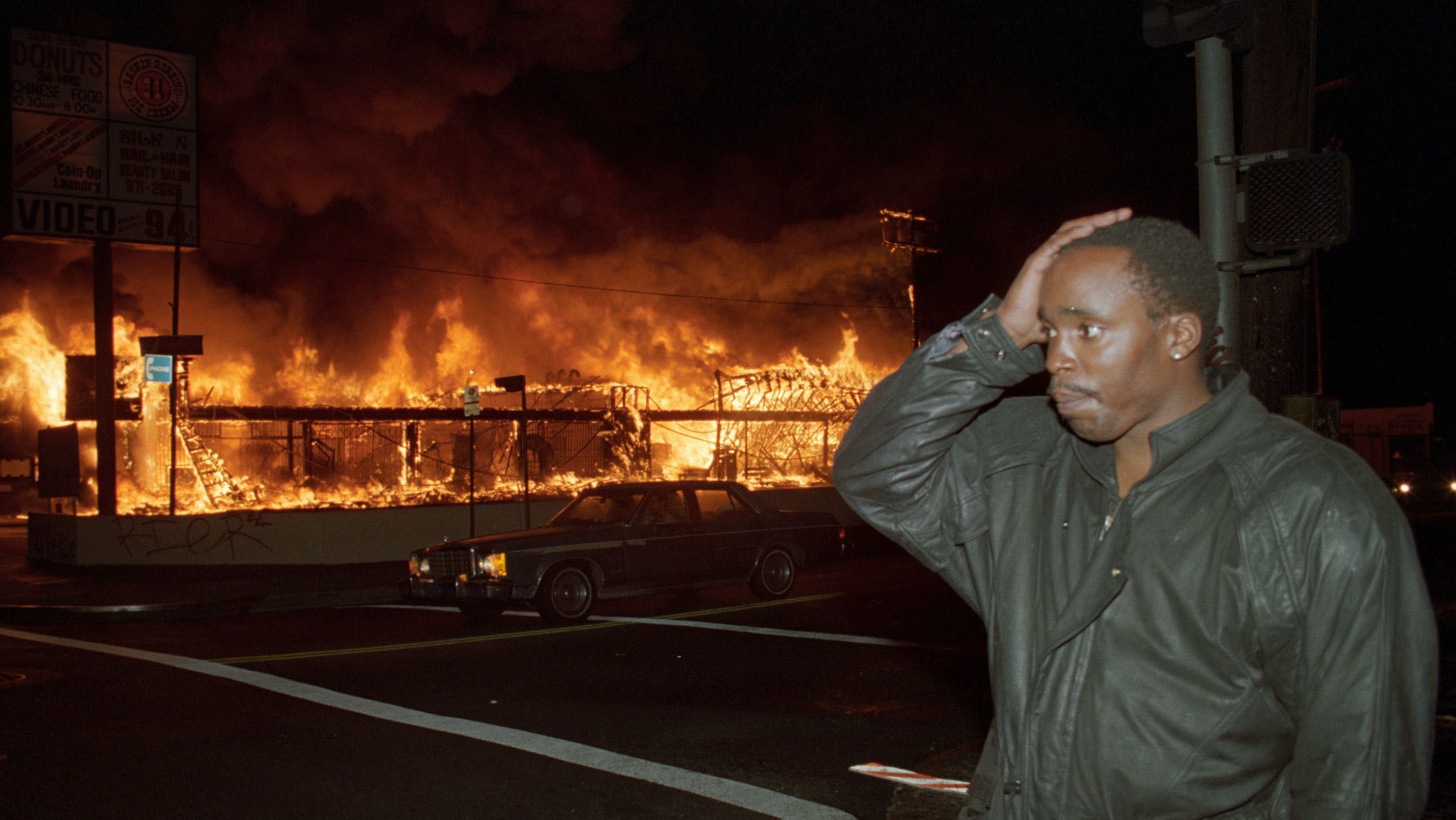 A businessman holds his hand to his head as the store he owns burns down across the street from him during the Los Angeles Riots in the ealy morning hours of April 30, 1992.  Dozens of arson fires were set in south-central Los Angeles after the acquittal of four LAPD officers in the videotaped beating of motorist Rodney King.   REUTERS/Lee Celano  (UNITED STATES - Tags: CIVIL UNREST CRIME LAW) - RTR30E2P