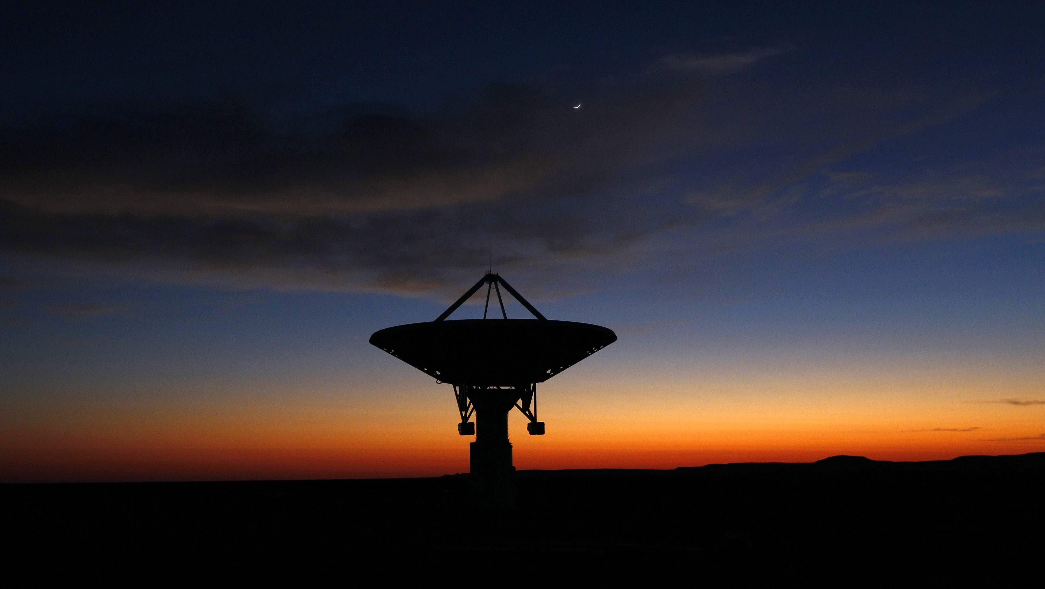 Dawn breaks over a radio telescope dish of the KAT-7 Array pointing skyward at the proposed South African site for the Square Kilometre Array (SKA) telescope near Carnavon in the country's remote Northern Cape province in this picture taken May 18, 2012. South Africa is bidding against Australia to host the SKA, which will be the world's largest radio telescope when completed. Picture taken May 18, 2012.