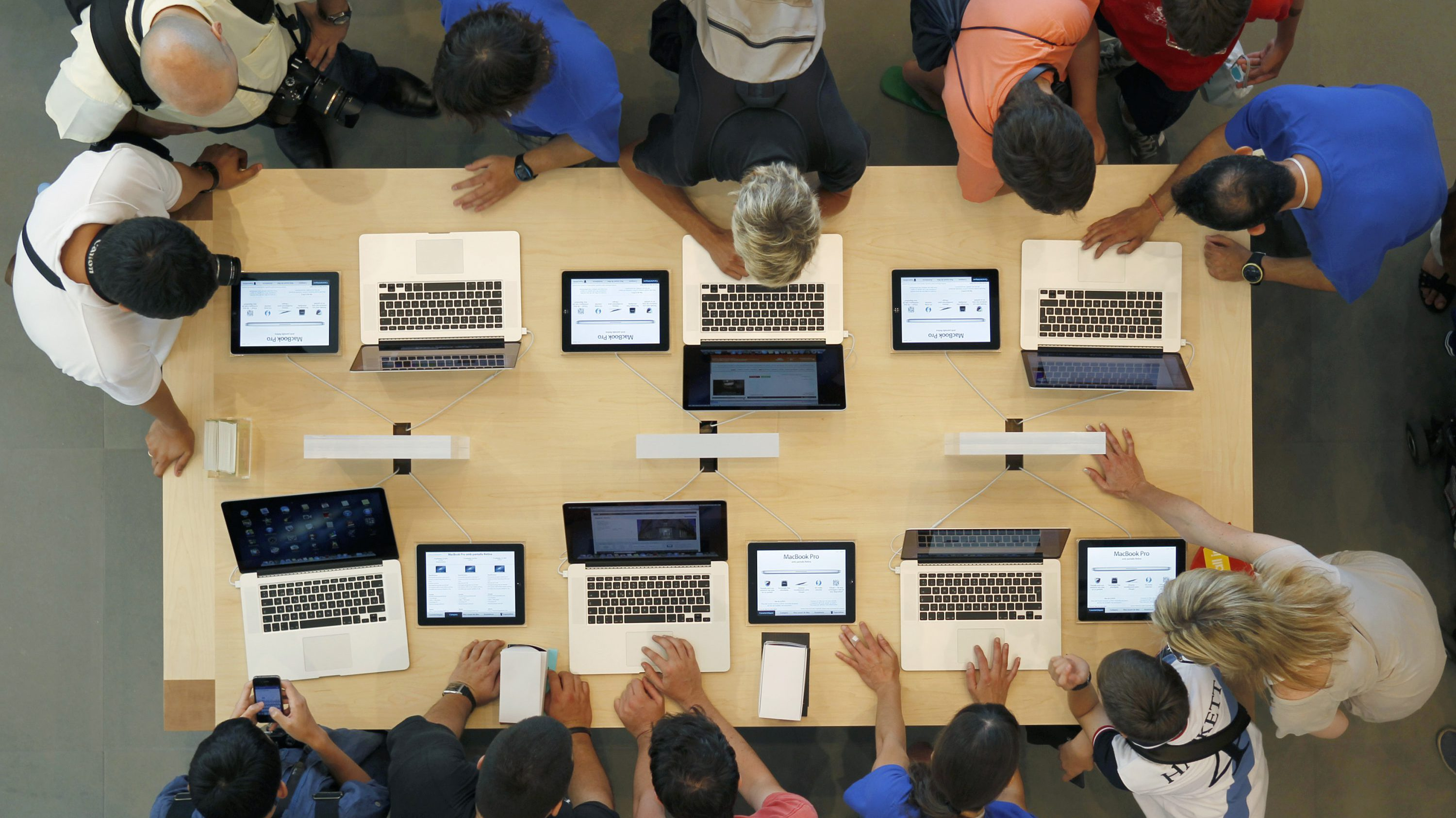 Employees And Customers Surround A Table With MacBook Pros, During The  Official Opening Of The