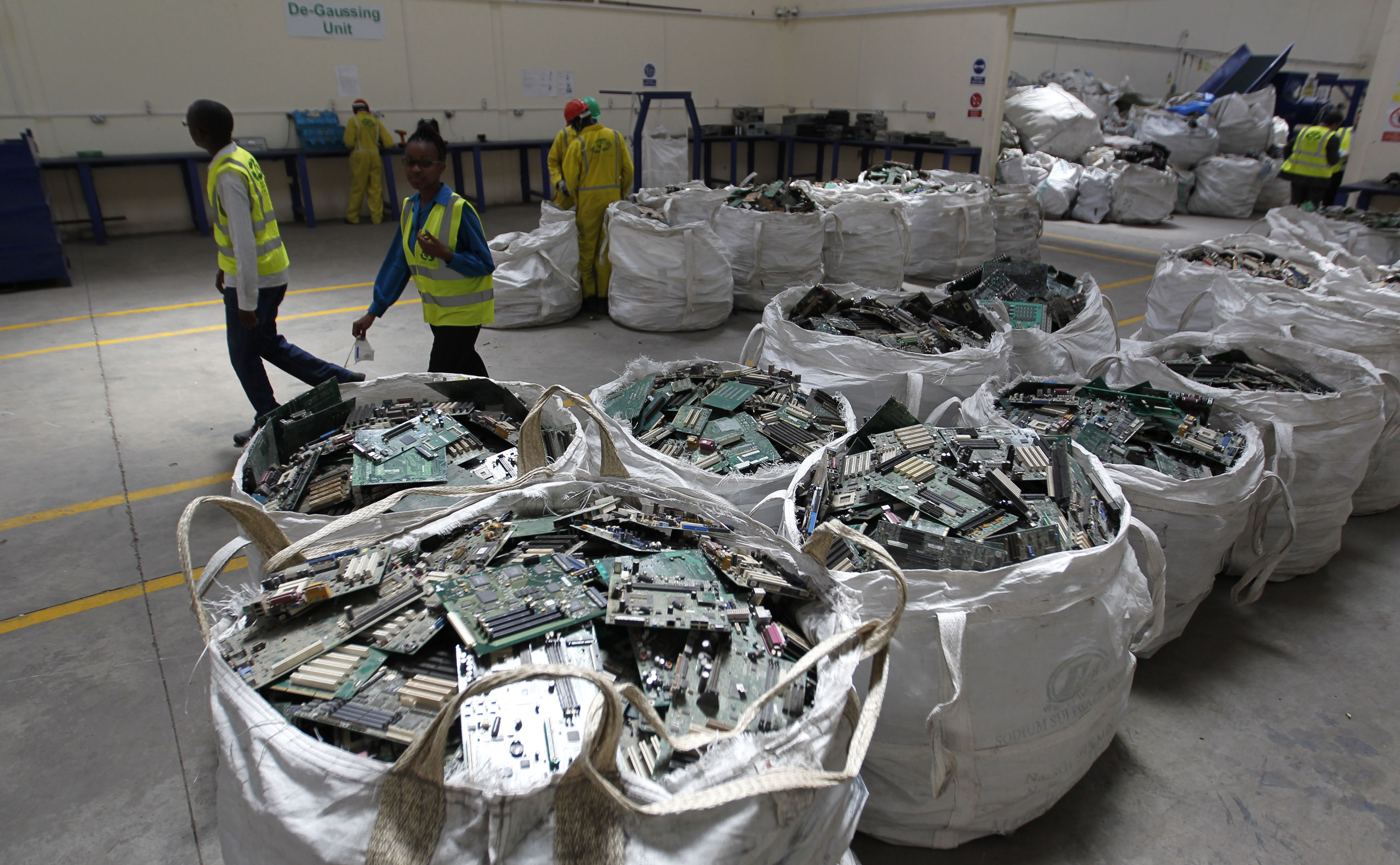Employees walk past sorted parts of discarded computers and other electronics for recycling at the EACR facility in Athi River near Kenya's capital Nairobi