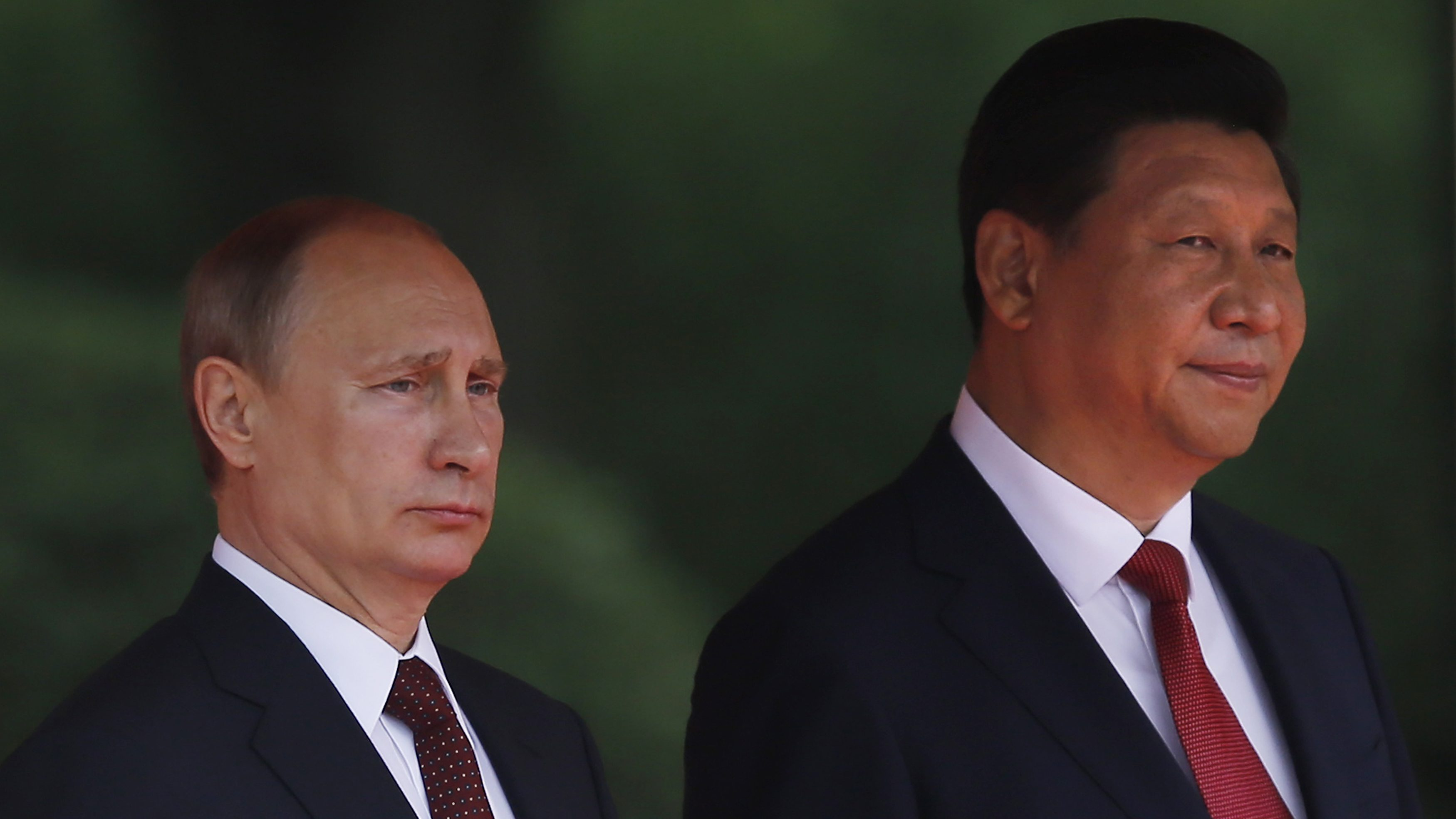 China's President Xi Jinping (R) and his Russian counterpart Vladimir Putin attend a welcoming ceremony at the Xijiao State Guesthouse, before the fourth Conference on Interaction and Confidence Building Measures in Asia (CICA) summit in Shanghai May 20, 2014. Trade between China and Russia is expected to reach $100 billion by 2015, Xi said on Tuesday, after meeting with Putin.