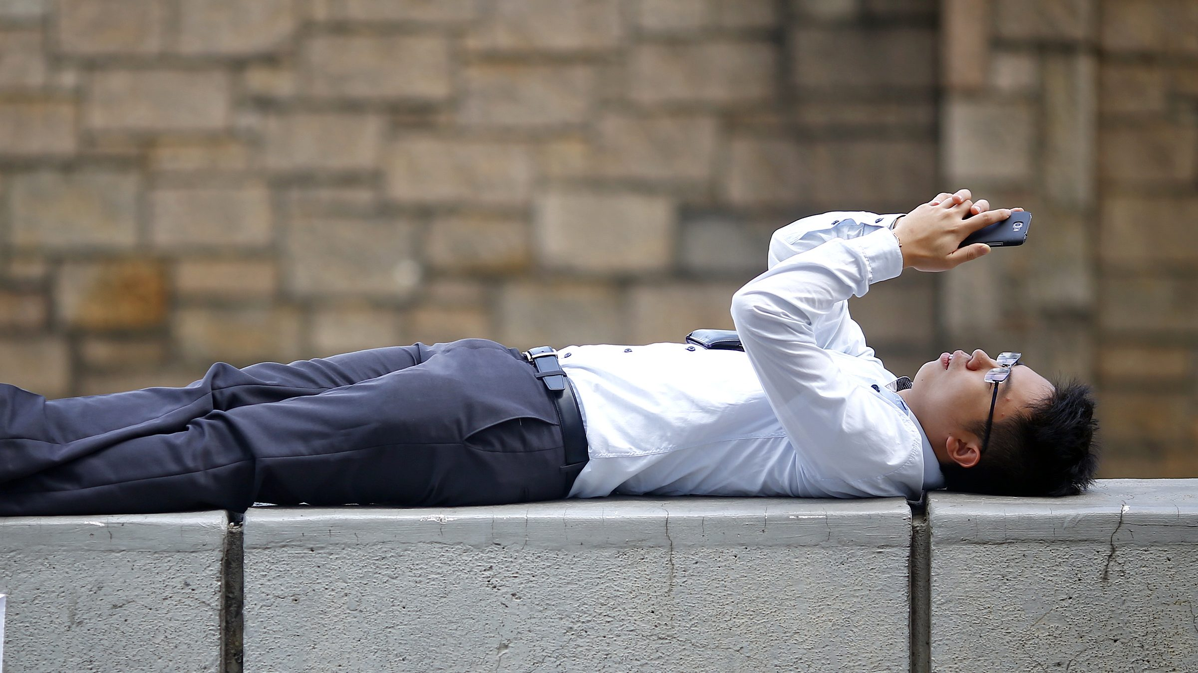 A businessman relaxes on a barrier between closed roads in the part of Hong Kong's financial central district pro-democracy protesters are occupying October 31, 2014. The former British colony of Hong Kong, which returned to Chinese rule in 1997, has witnessed a month of protests calling on the Beijing-backed government to keep its promise of introducing universal suffrage. The protests have for the most part been peaceful, with occasional clashes between the student-led protesters and Beijing supporters seeking to move them from the streets.