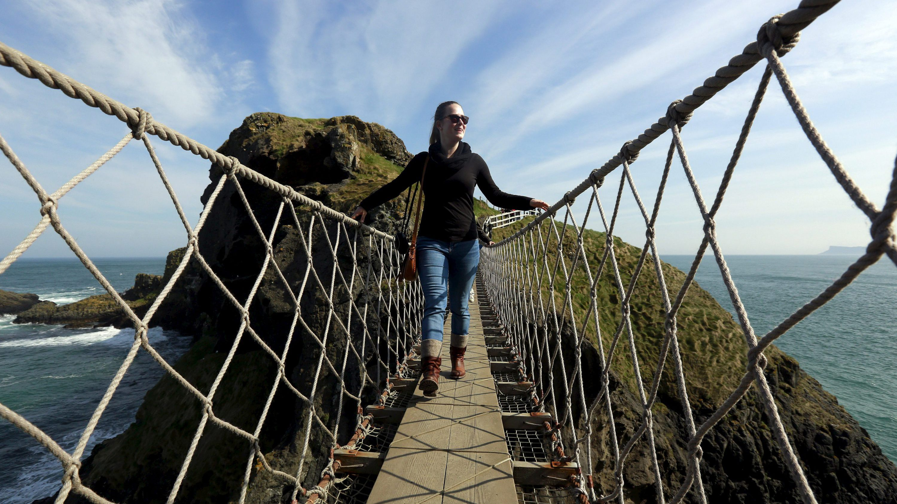 A tourist makes her way across Carrick-a-Rede Rope Bridge on the Causeway coast, north of Belfast April 8, 2015. The bridge is suspended 30 metres above sea level and was built 350 years ago by salmon fishermen, according to conservation organisation National Trust.
