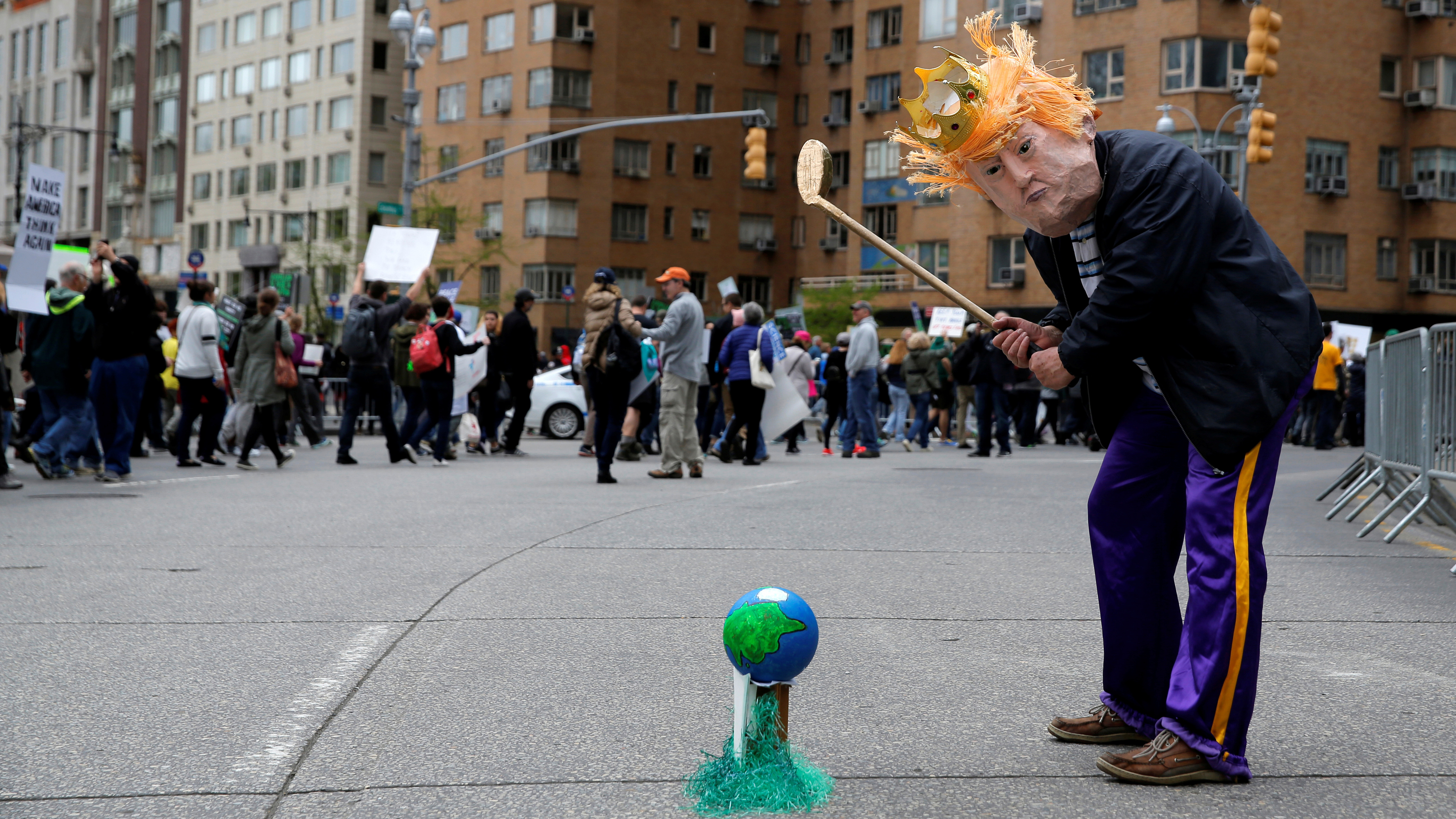 A protester dressed as U.S. president Donald Trump pretends to play golf with the Earth during the Earth Day 'March For Science NYC' demonstration to coincide with similar marches globally in Manhattan, New York, U.S., April 22, 2017.  REUTERS/Andrew Kelly - RTS13G00