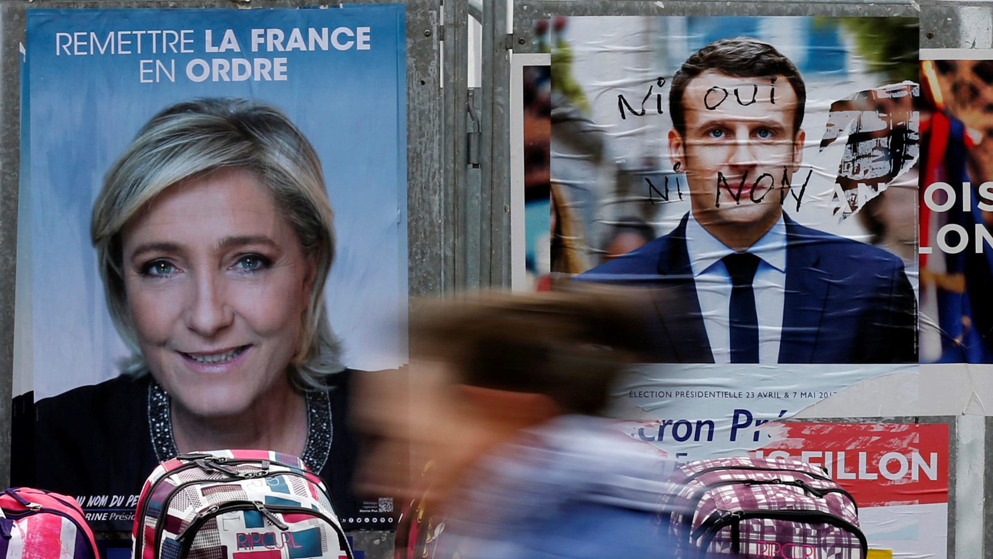 A woman walks past official posters of candidates for the 2017 French presidential election Marine Le Pen, French National Front (FN) political party leader (L) and Emmanuel Macron, head of the political movement En Marche !, or Onwards !, (R) on a local market in Bethune, France April 24, 2017.