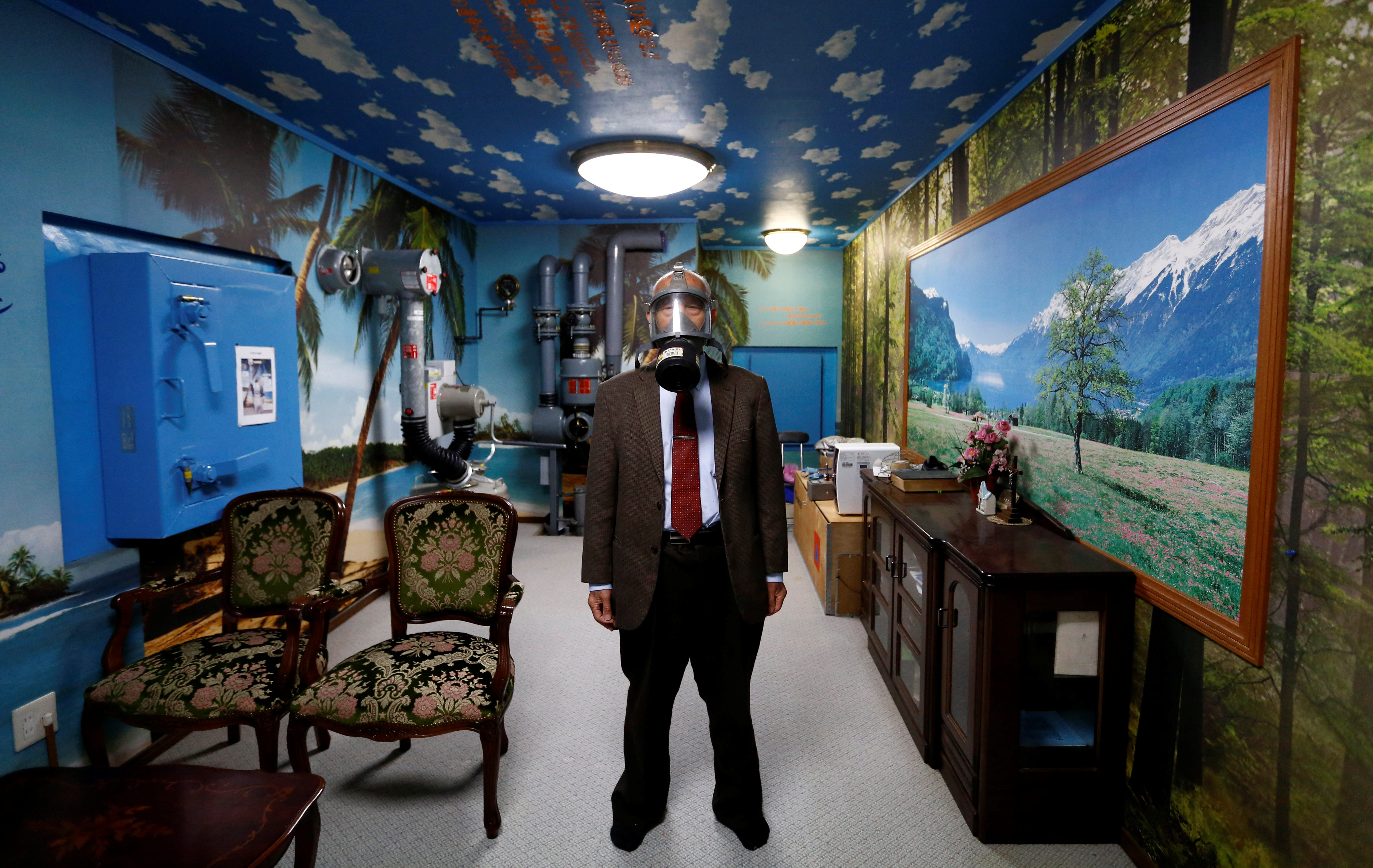 Seiichiro Nishimoto, CEO of Shelter Co., poses wearing a gas mask at a model room for the companyÕs nuclear shelters in the basement of his house in Osaka