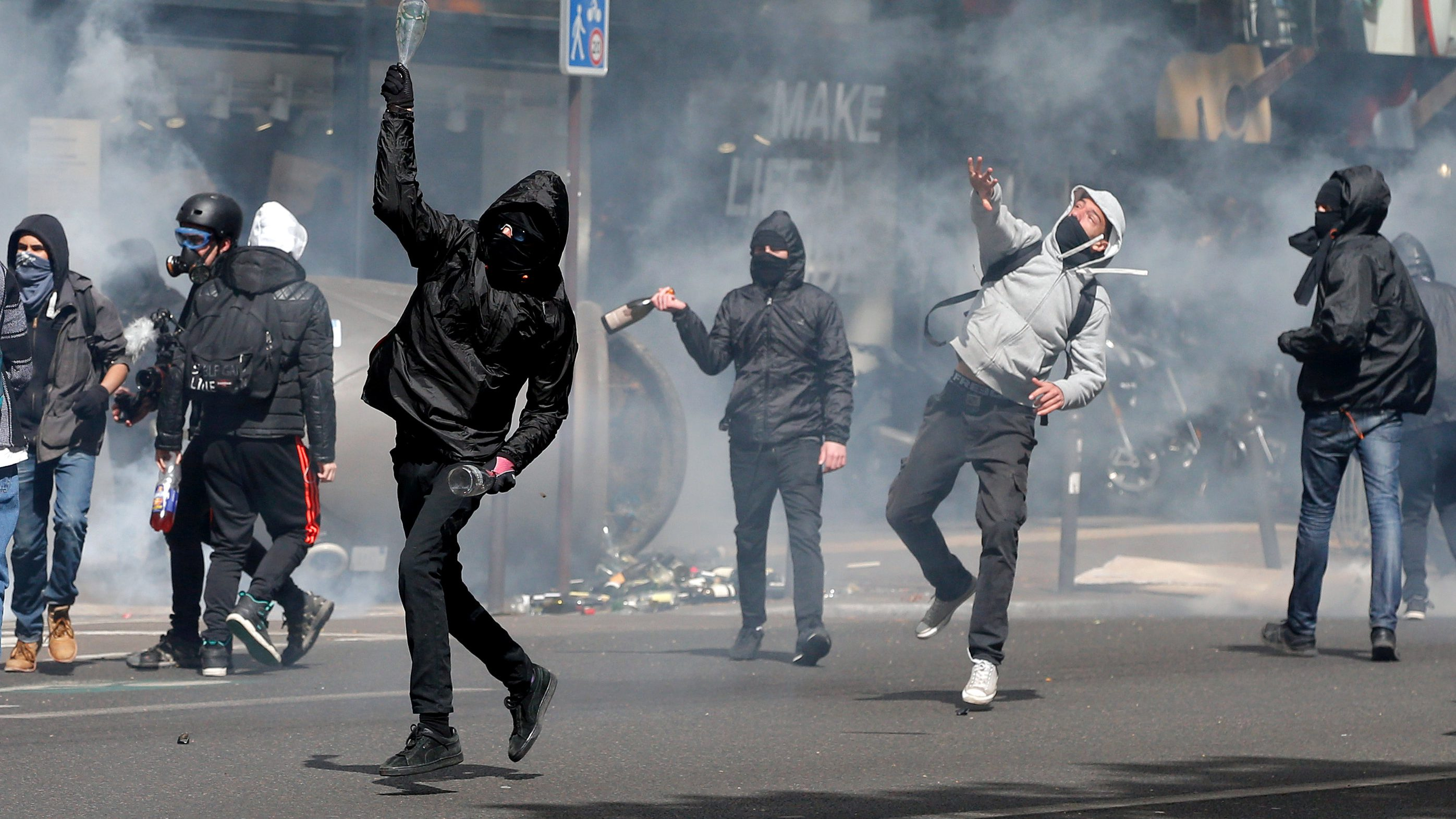 Hooded youths throw bottles during a demonstration to protest the results of the first round of the presidential election in Paris