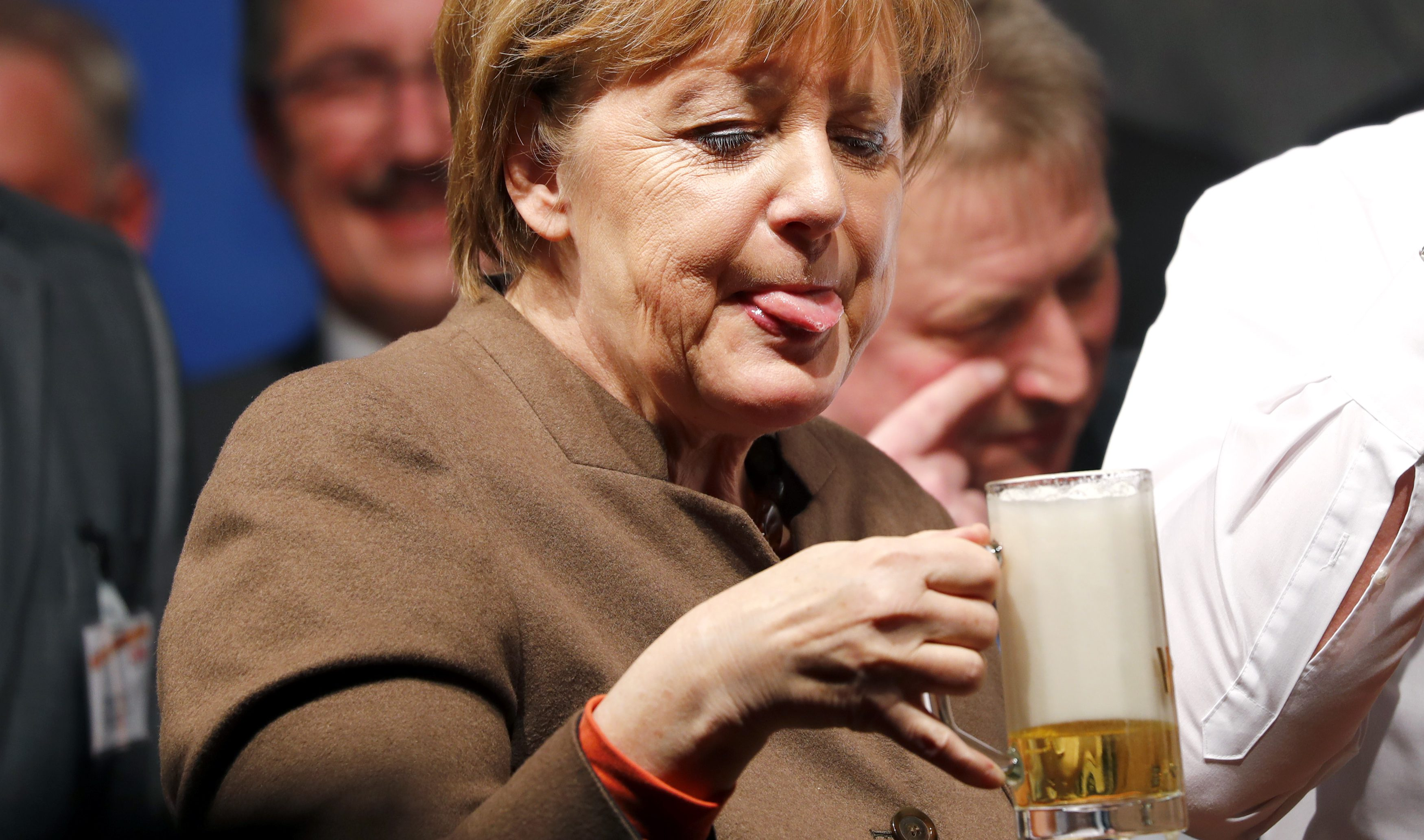 German Chancellor Angela Merkel enjoys a beer during the Christain Democratic Union (CDU) political Ash Wednesday meeting in Volkmarsen, Germany February 29, 2016.    TPX IMAGES OF THE DAY - RTS8MW0