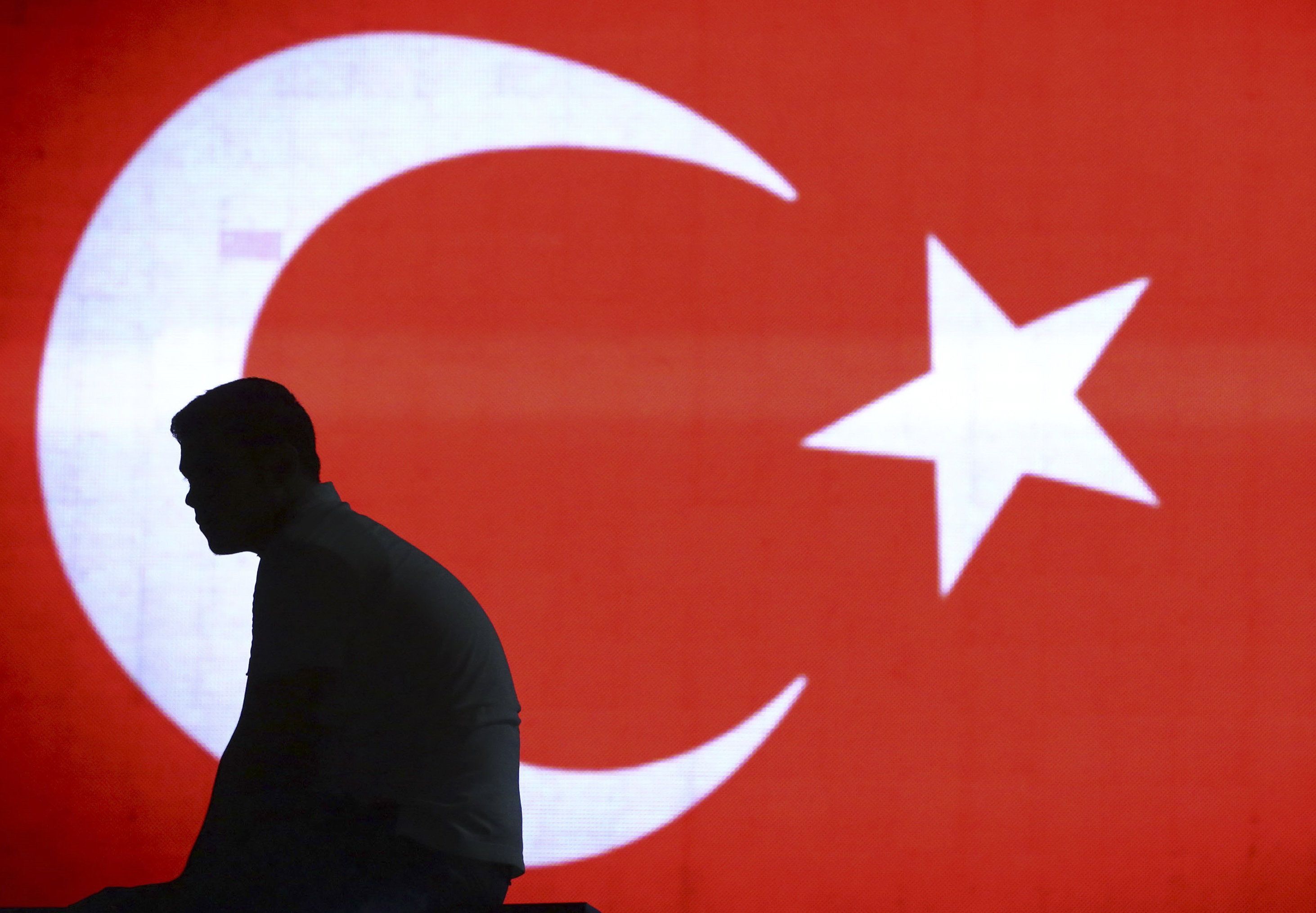 A man is silhouetted against a giant Turkish flag in Istanbul airport, Turkey, July 16, 2016.    REUTERS/Huseyin Aldemir   TPX IMAGES OF THE DAY - RTSIA0W