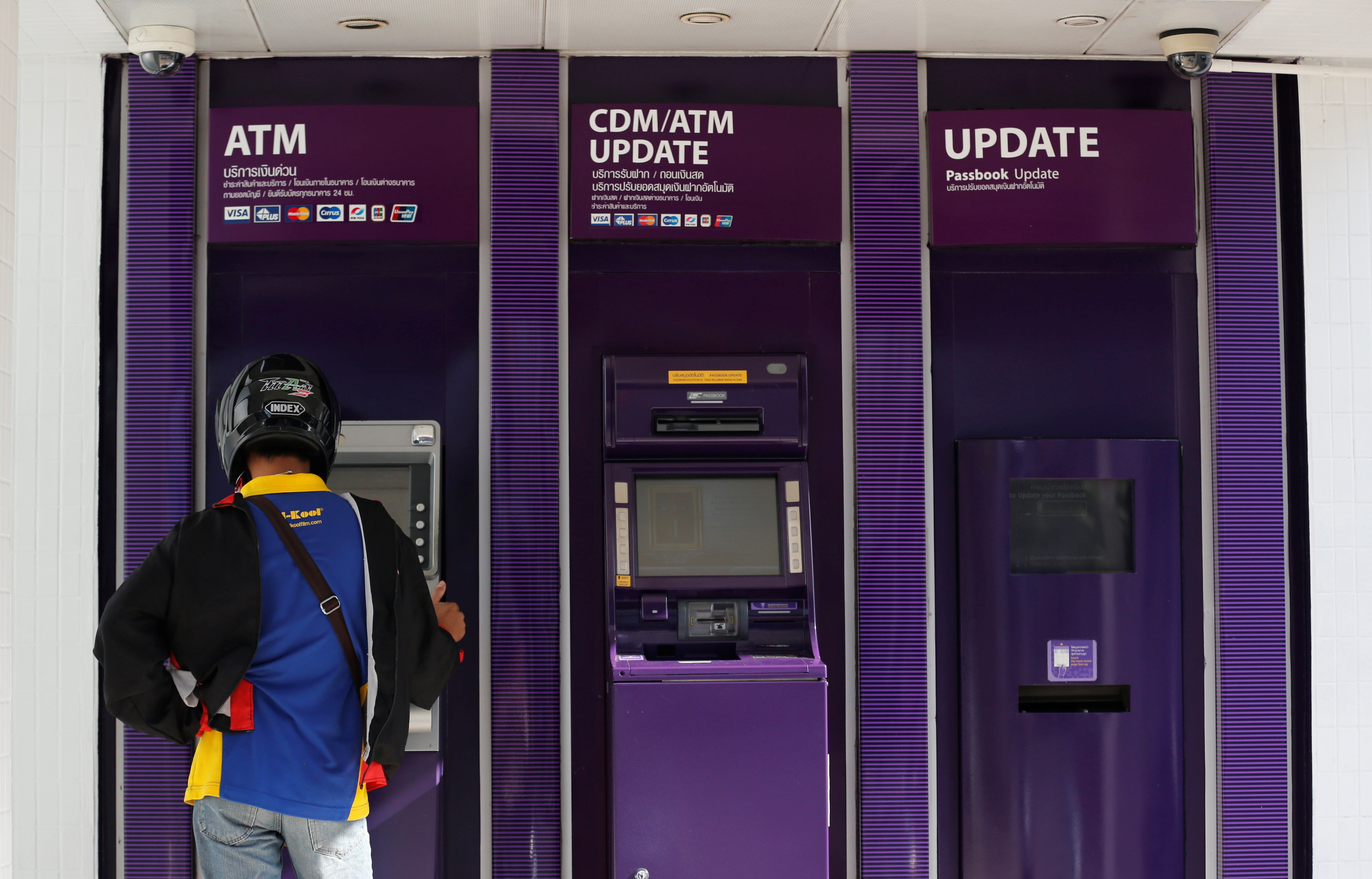 A man uses an ATM machine at the Siam Commercial Bank branch in central Bangkok, Thailand, January 23, 2017. REUTERS/Chaiwat Subprasom - RTSWXOX