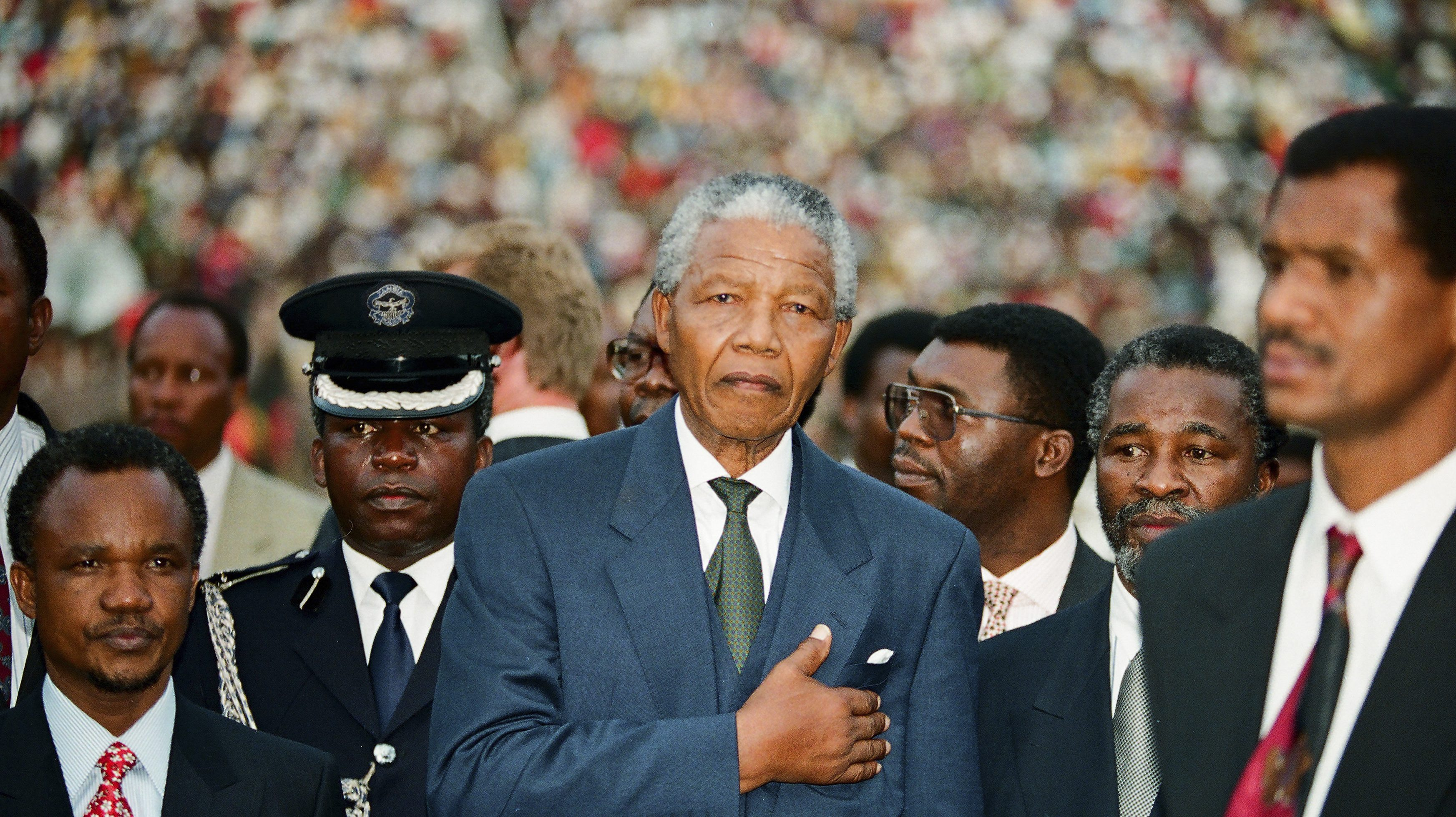 The newly sworn in first black President of South Africa Nelson Mandela keeps his hand on his hart as he listens to the national anthem near the Union building in Pretoria, May 10, 1994.