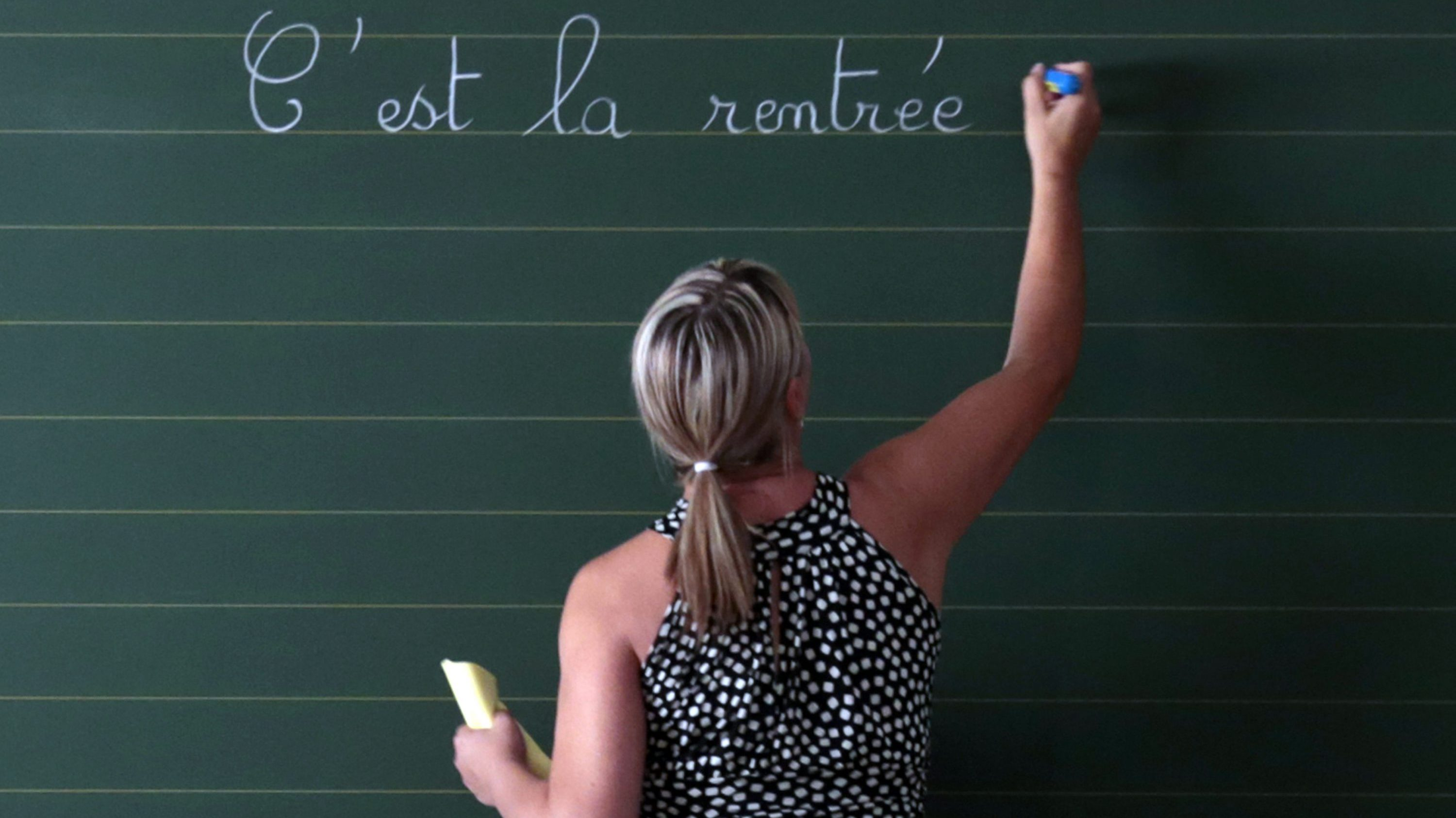 """A teacher writes the phrase """"Today it is the start of the new school year"""" on the blackboard of her classroom on the first day of the new school year at a primary school in Nice, September 3, 2013."""