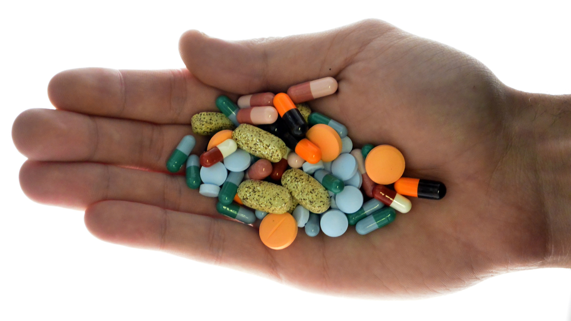 A person holds pharmaceutical tablets and capsules