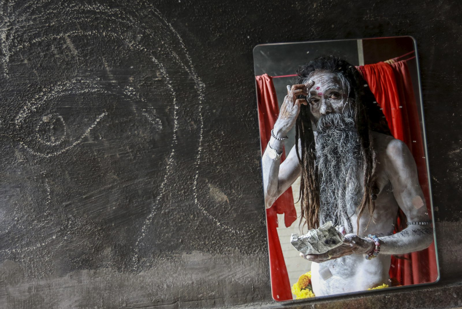 A Naga sadhu, or a Hindu holy man, applies ash at his camp before a procession during Kumbh Mela or the Pitcher Festival in Trimbakeshwar, India, August 27, 2015. Hundreds of thousands of Hindus took part in the religious gathering at the banks of the Godavari river in Nashik city at the festival, which is held every 12 years in different Indian cities.