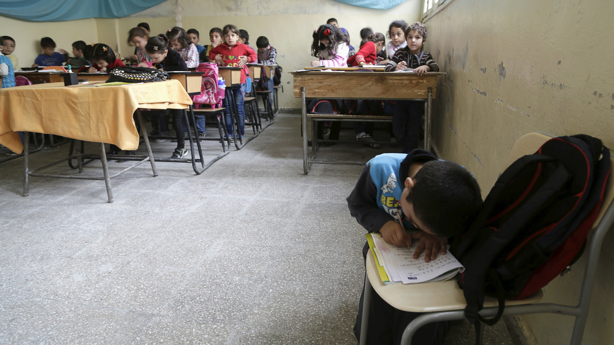 A student uses a seat as a desk in an overcrowded class inside Hosam Kamel school in the rebel-controlled area of Maaret al-Numan town in Idlib province, Syria October 28, 2015.