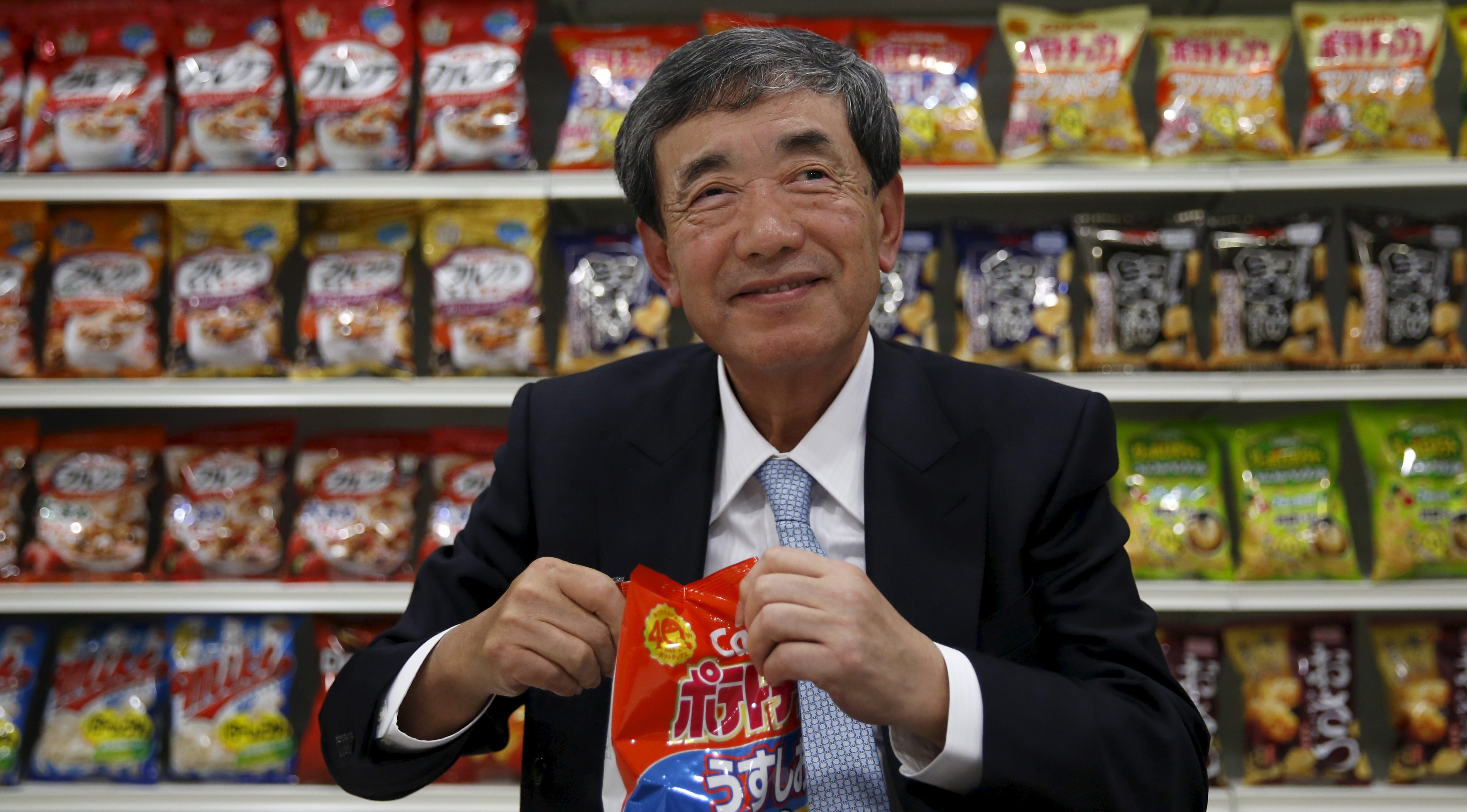 Akira Matsumoto, chairman and chief executive of Calbee, opens a pack of potato chips at the company headquarters in Tokyo, Japan, January 15, 2016.