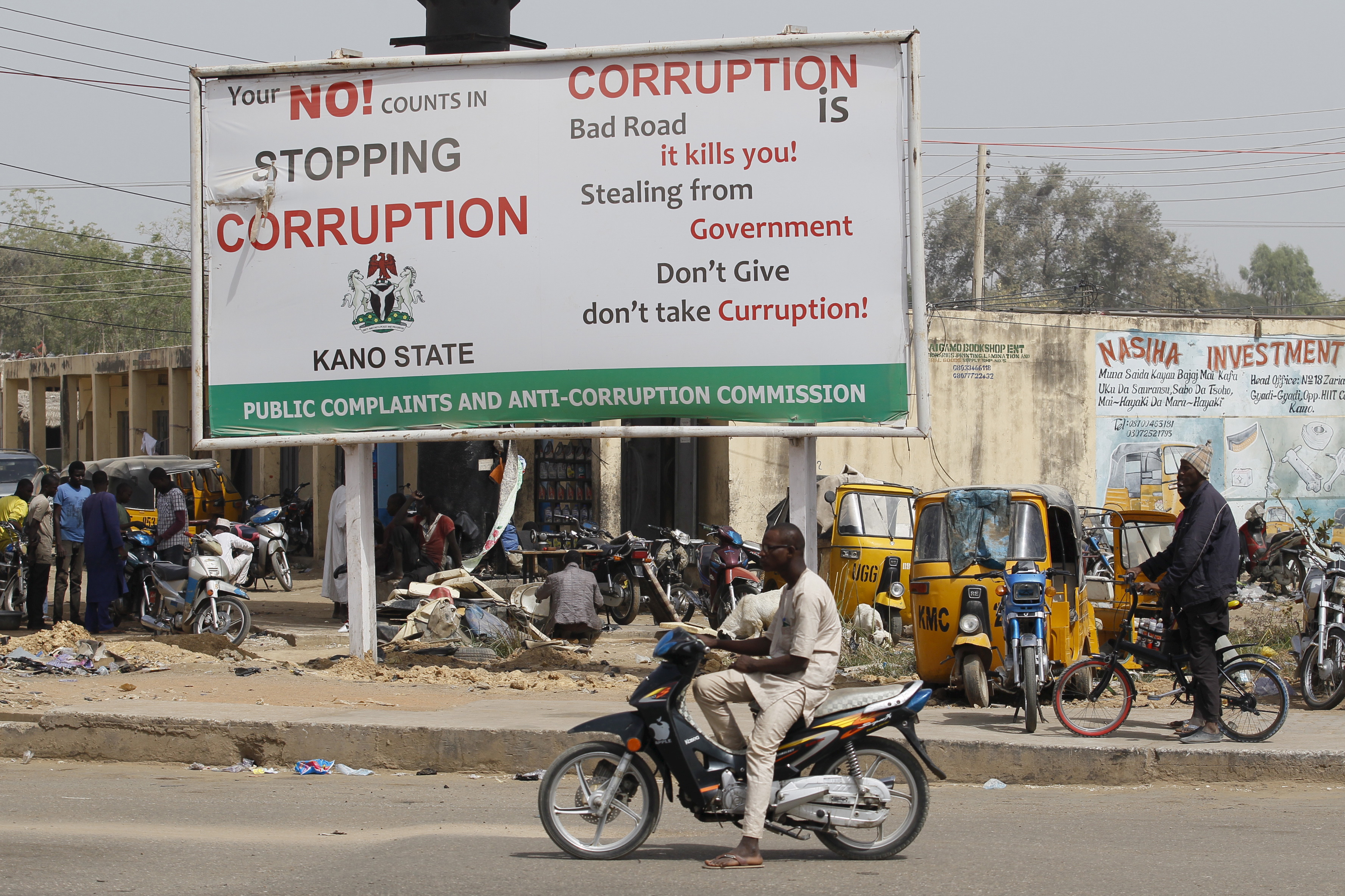A man on a motorcycle sits near a signboard campaigning against corruption along a road in Dangi district in Nigeria's northern city of Kano, January 19, 2016. True to his election promises, Nigerian President Muhammadu Buhari has gone all out on corruption, alleging mind-boggling sums plundered from state coffers and giving investigators licence to pull in big hitters once thought untouchable. Now comes the hard part: making the charges stick. The first test comes on Wednesday with the opening of the trial of former National Security Advisor Sambo Dasuki, accused of fraud over $68 million of defence spending, part of a wider $2.1 billion in arms deals under scrutiny.