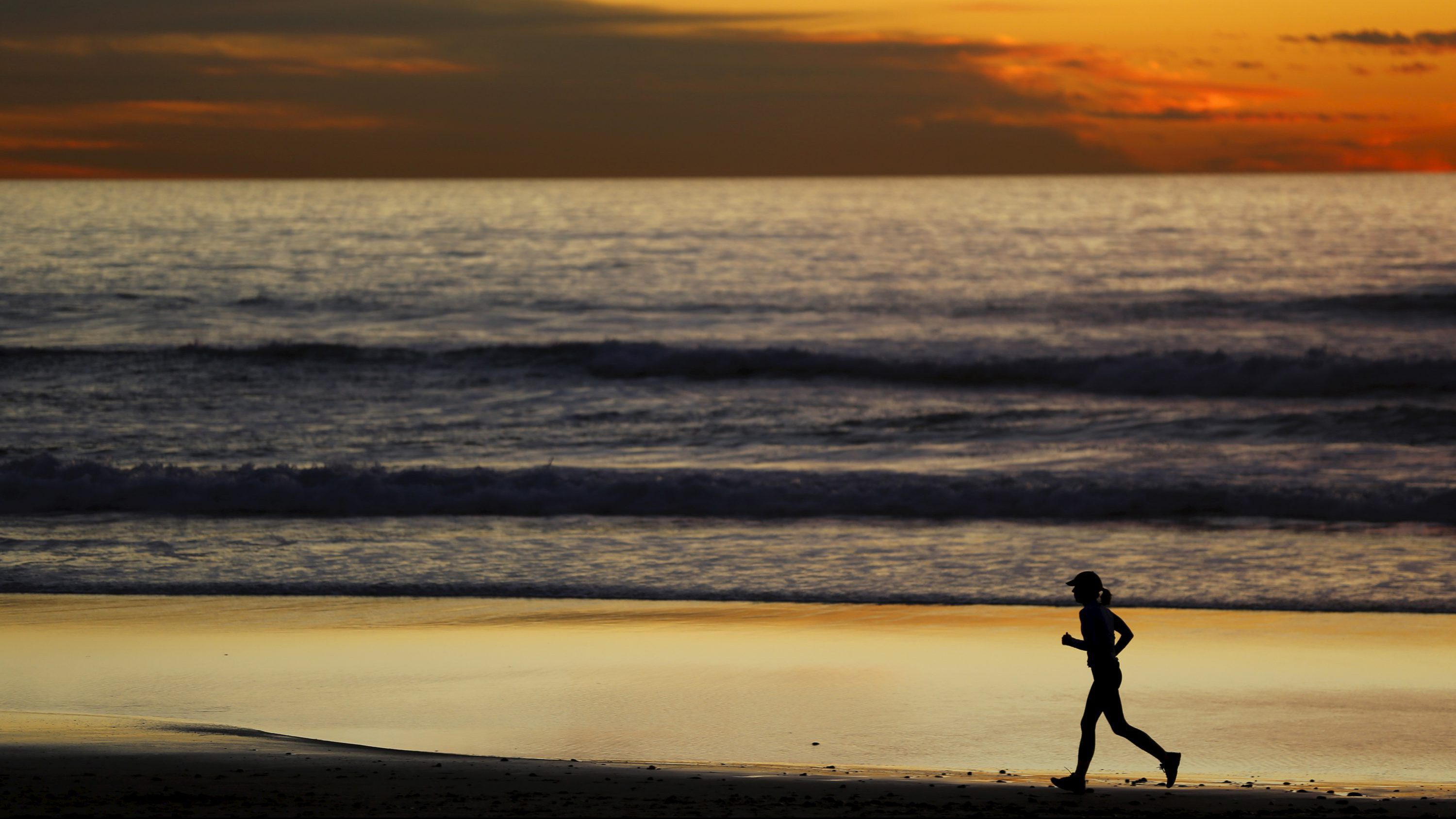 A woman jogs along the beach after sunset in Cardiff, California January 27, 2016.