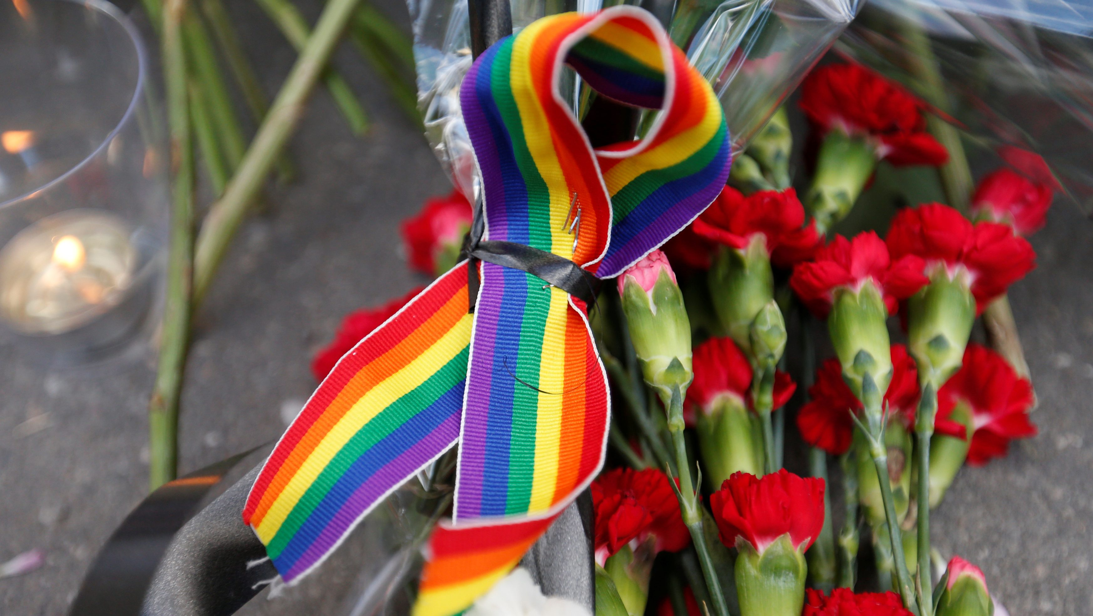 A rainbow ribbon, a candle and flowers for the victims of the shooting at a gay nightclub in Orlando are seen in front of the U.S. Embassy in Moscow, Russia, June 13, 2016. REUTERS/Maxim Zmeyev - RTX2G011
