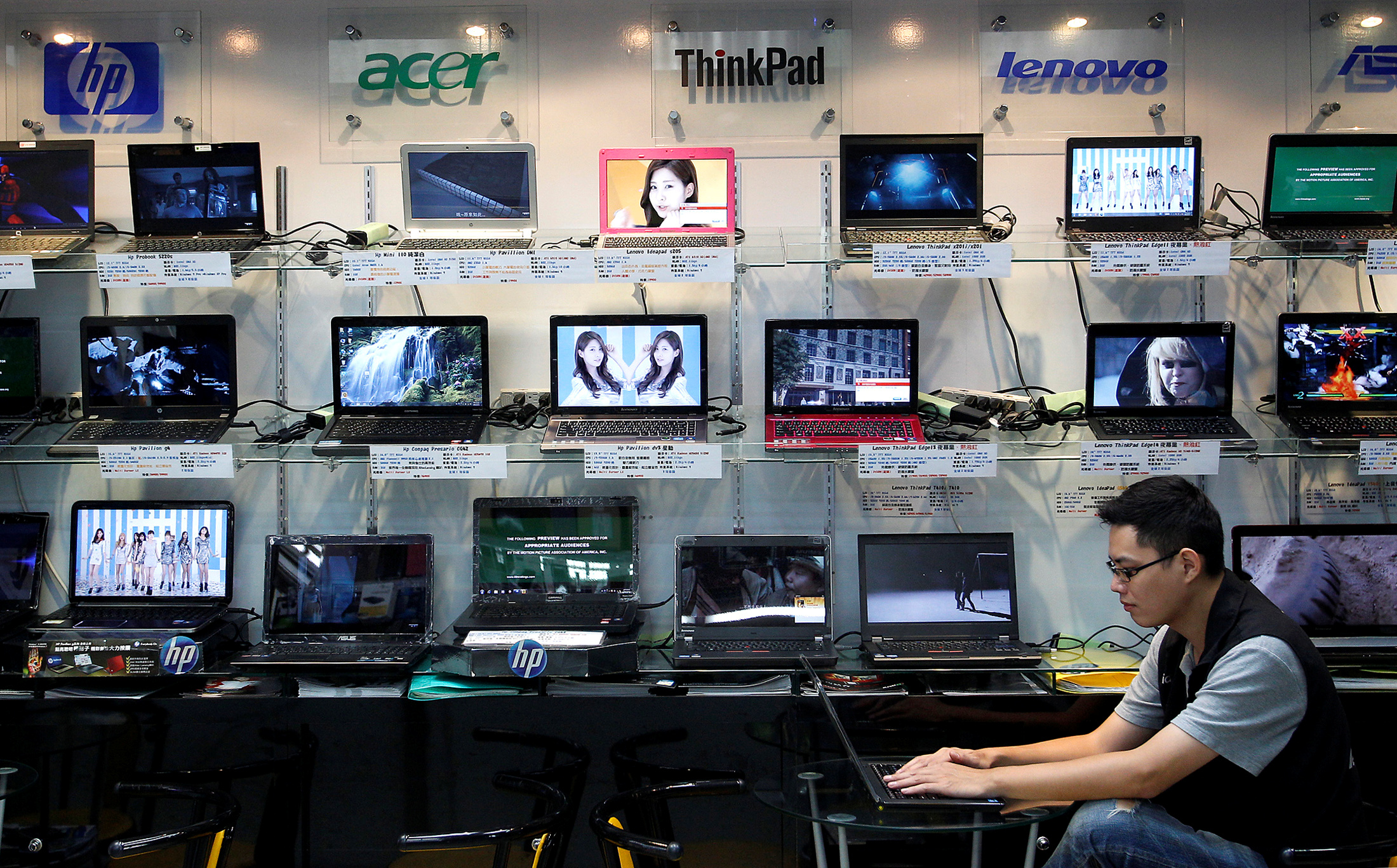 A shop attendant sits in front of a wall of laptops at a computer mall in Taipei August 31, 2011.