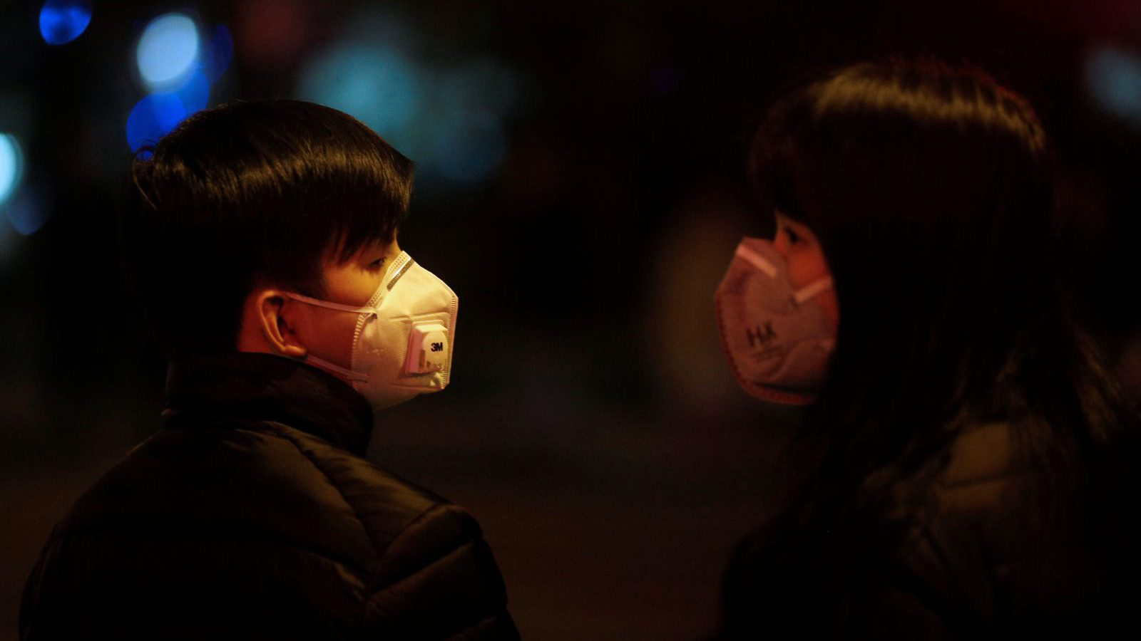 A couple wears masks on a street amid heavy smog in downtown Shanghai