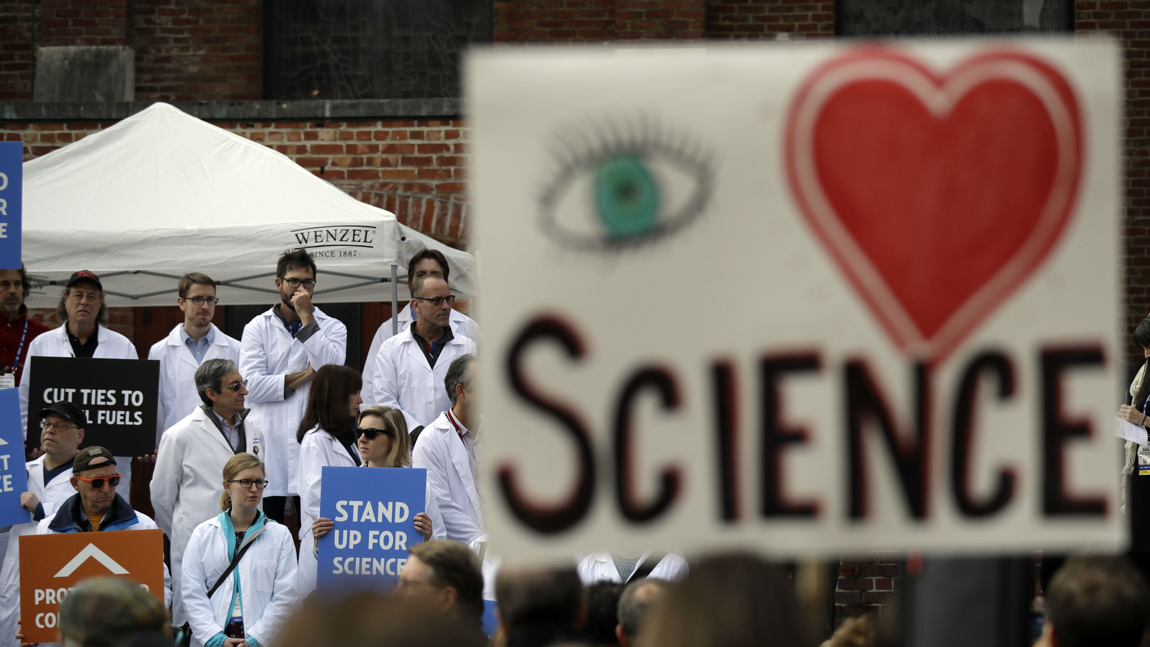 "a large ""I heart Science"" poster at a climate rally."