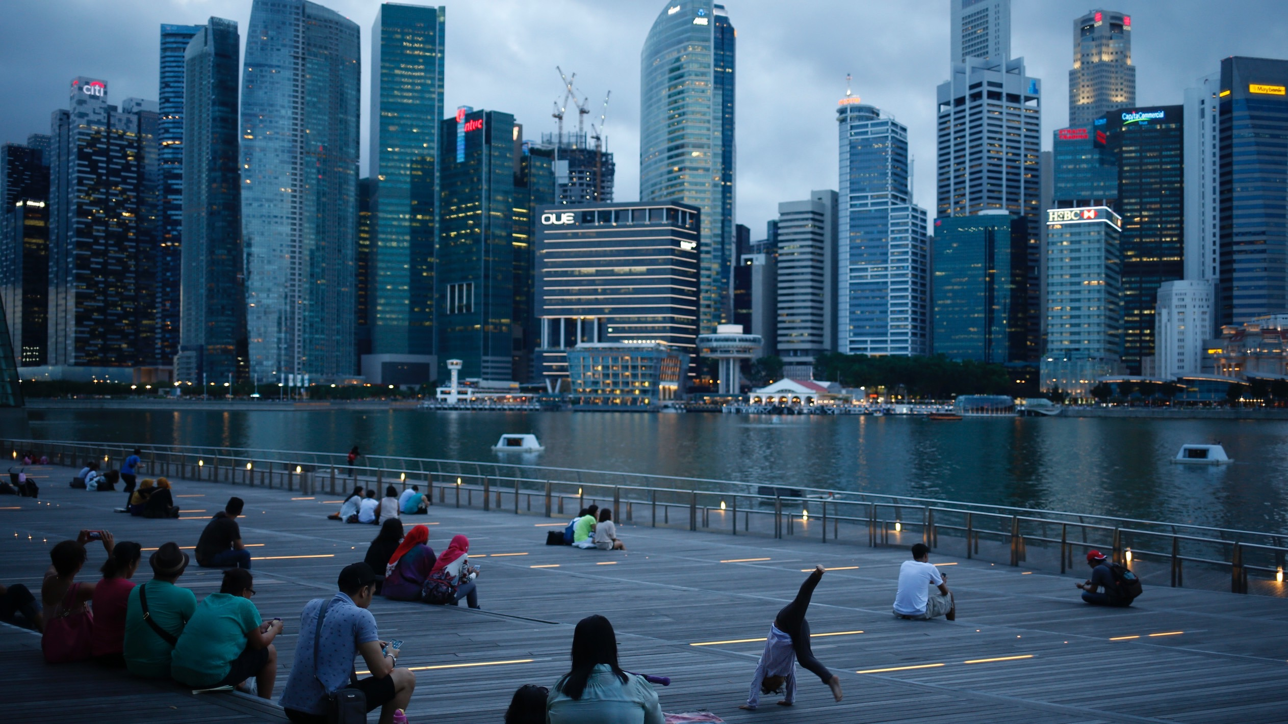 People wait to watch a laser light show along Marina Bay overlooking the central business district in the evening in Singapore