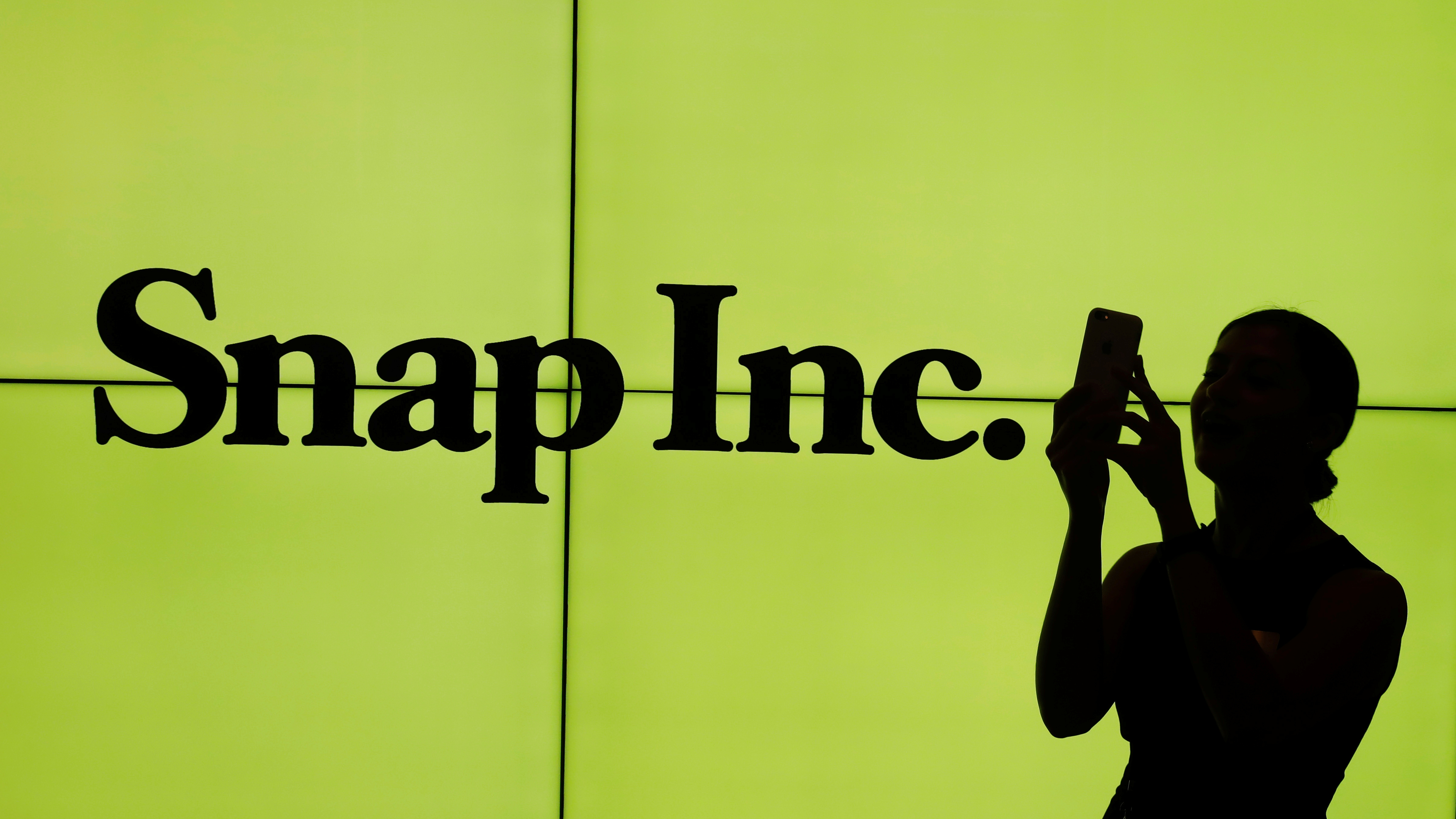 A woman stands in front of the logo of Snap Inc. on the floor of the New York Stock Exchange (NYSE) while waiting for Snap Inc. to post their IPO, in New York City, NY, U.S. March 2, 2017. REUTERS/Lucas Jackson     TPX IMAGES OF THE DAY - RTS116C3