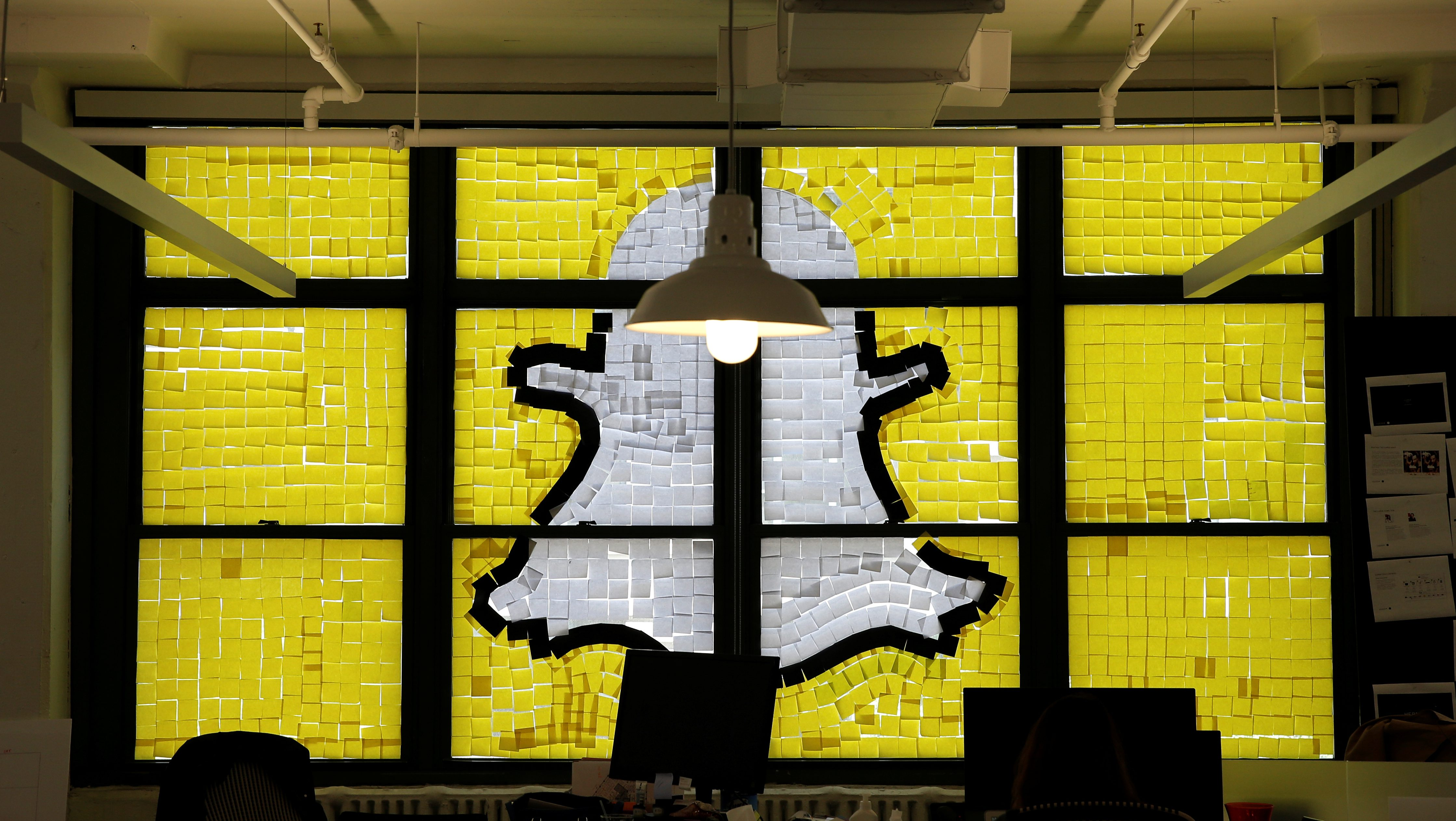 "Snapchat logo image created with Post-it notes is seen in the windows of Havas Worldwide offices at 200 Hudson street in lower Manhattan, New York during ""Post-it note war"""
