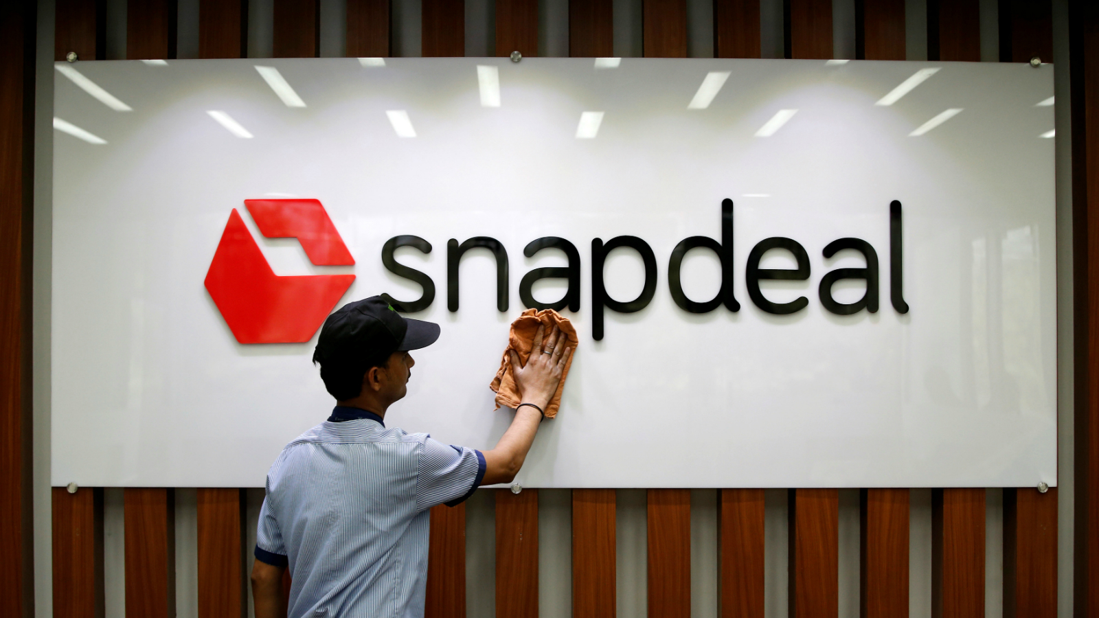 An employee cleans a Snapdeal logo at its headquarters in Gurugram on the outskirts of New Delhi, India, April 3, 2017. Picture taken April 3.