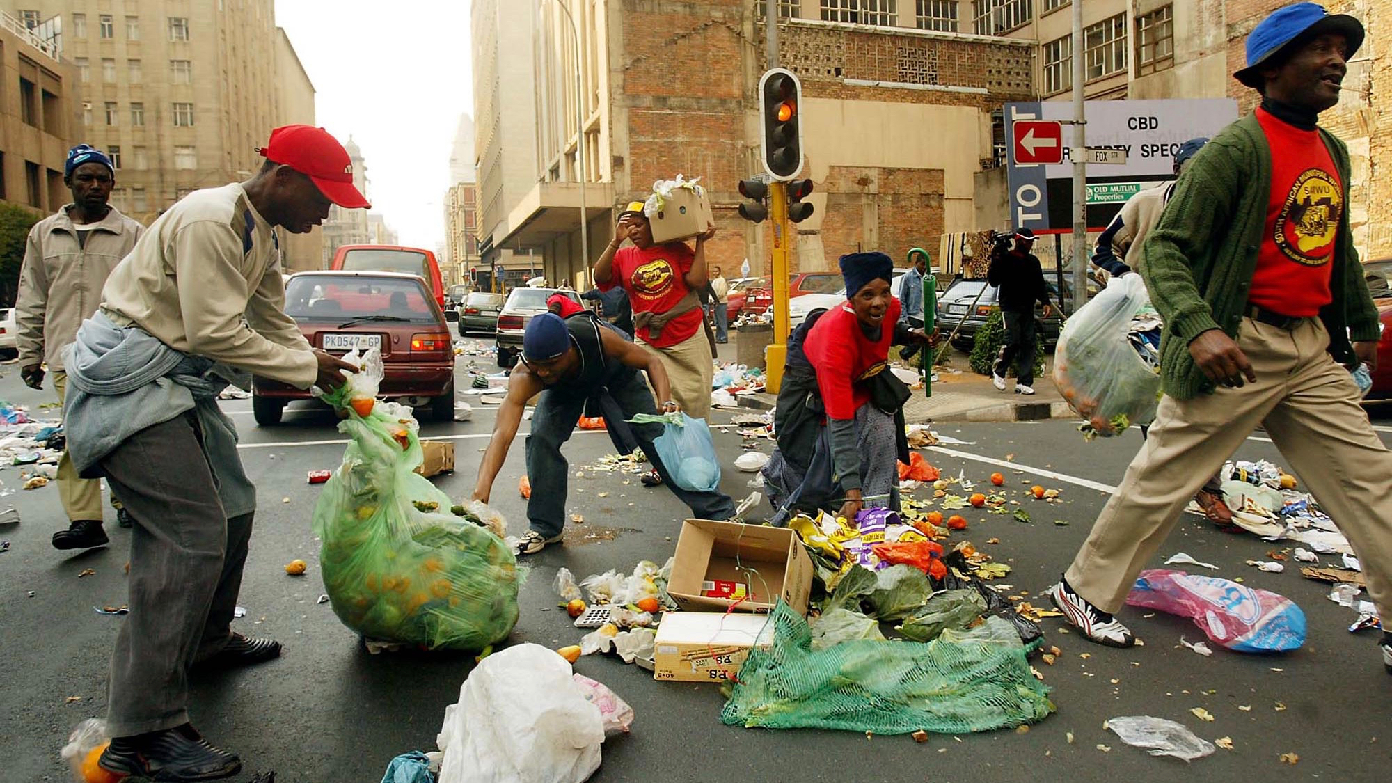 Striking municipal workers trash the streets as they protest in downtown Johannesburg, Thursday Aug. 11, 2005. The strike is part of a wave of industrial unrest involving airline staff, goldminers, shop assistants and the municipal workers angry that the economic benefits of apartheid's demise have been slow to filter down. (AP PhotO)