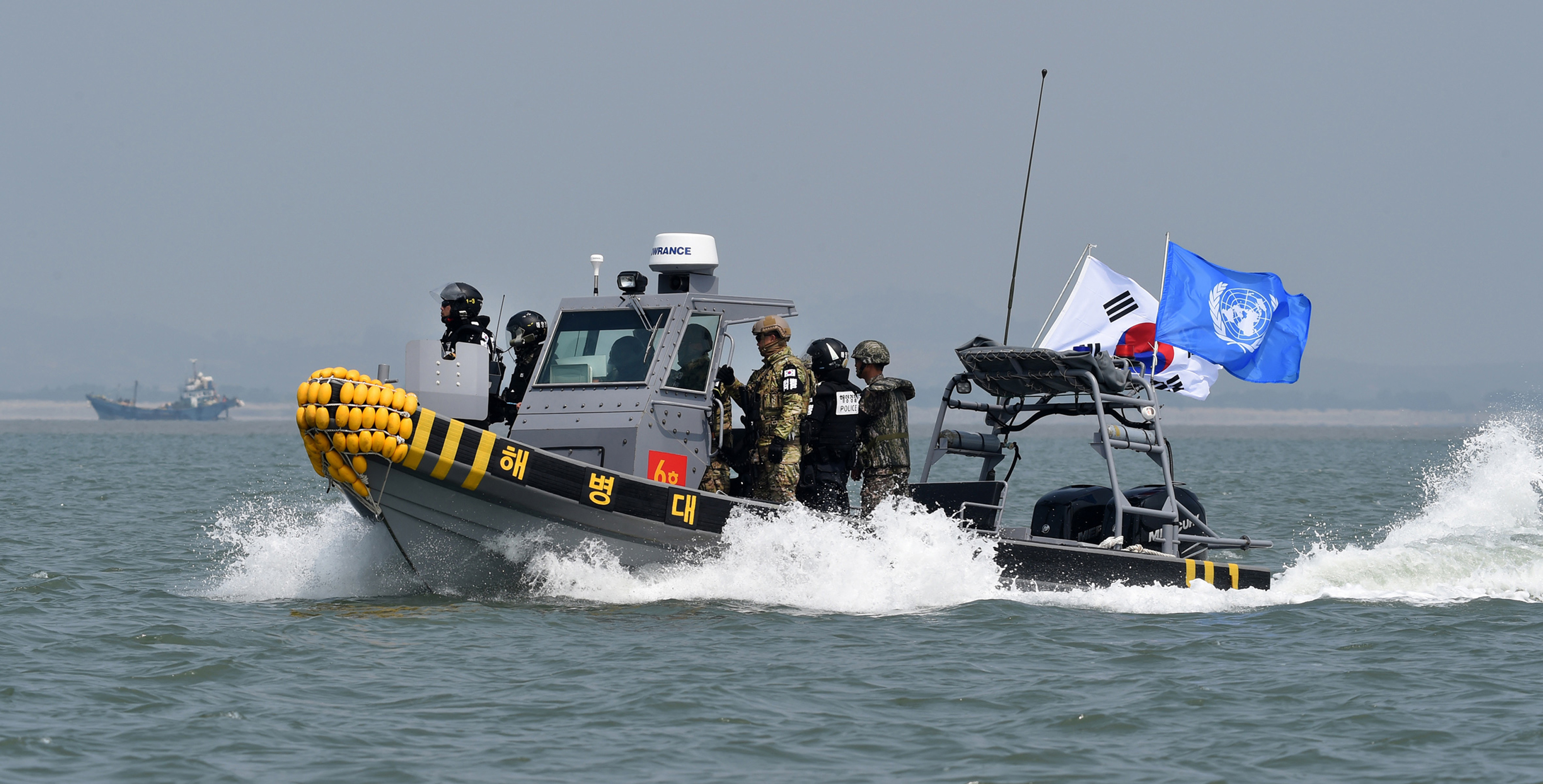 In this photo provided by the South Korean Defense Ministry, South Korean marines and navy soldiers on a boat conduct a crackdown against China's illegal fishing in neutral waters around Ganghwa island, South Korea, Friday, June 10, 2016. South Korean military vessels started an operation Friday to repel Chinese fishing boats illegally harvesting prized blue crabs from an area near Seoul's disputed sea boundary with North Korea.