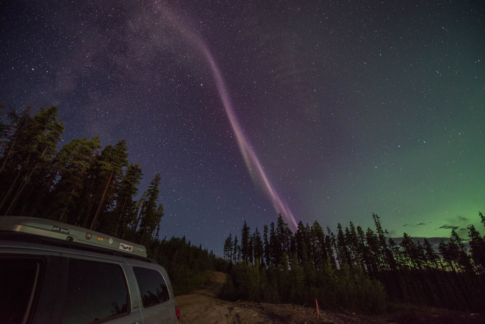 A pink Steve against a dark sky with green northern lights.