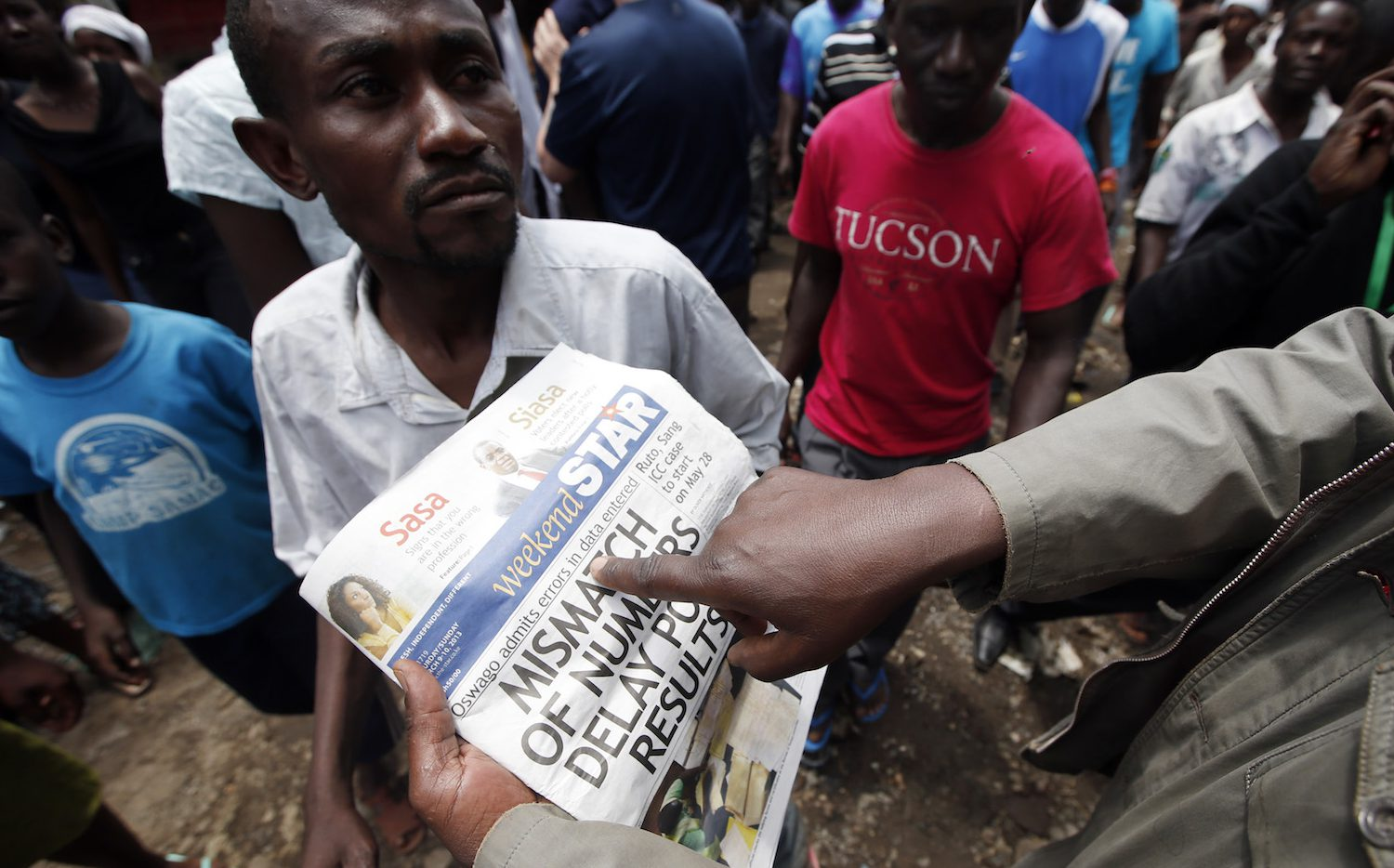 Supporters of Kenyan Prime Minister Raila Odinga look at a newspaper in the Mathare slum in the Kenyan capital of Nairobi March 9, 2013. Kenyan Prime Minister Raila Odinga will not concede this week's election and will launch a legal challenge if rival Uhuru Kenyatta is officially declared president, an adviser said on Saturday.