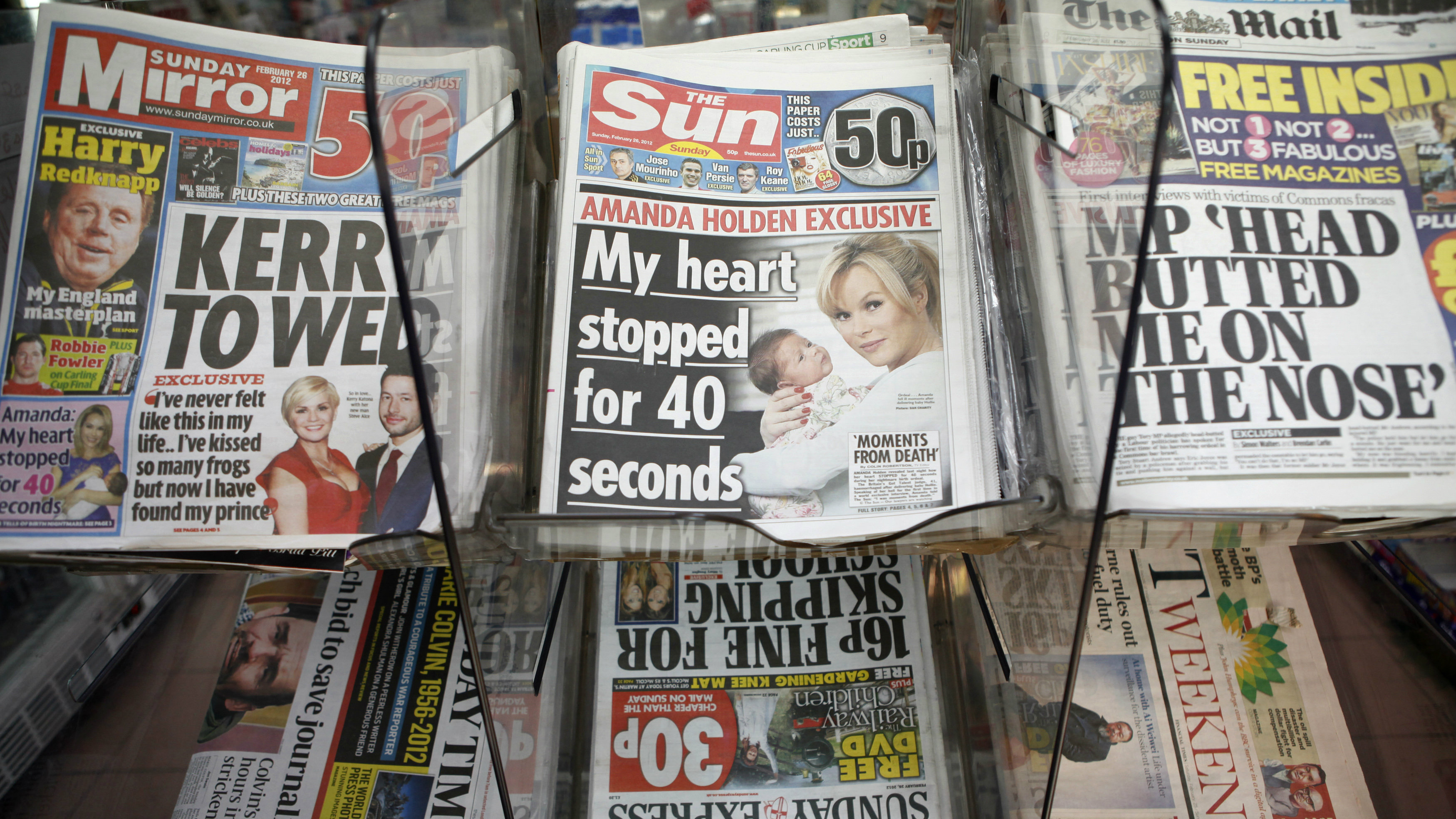 Copies of the Sun on Sunday are displayed for sale, on the first day of publication, in a newsagents in Wembley, north London February 26, 2012. Rupert Murdoch bid to grab back the huge audience his News Corp lost when it closed Britain's best-selling News of the World over a phone-hacking scandal with a new Sunday edition of his Sun tabloid filled with gossip, girls and celebrities. REUTERS/Andrew Winning (BRITAIN - Tags: MEDIA BUSINESS SOCIETY)