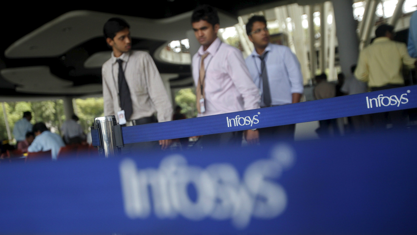 Employees of Indian software company Infosys walk past Infosys logos at their campus in the Electronic City area in Bangalore in this September 4, 2012 file photo.