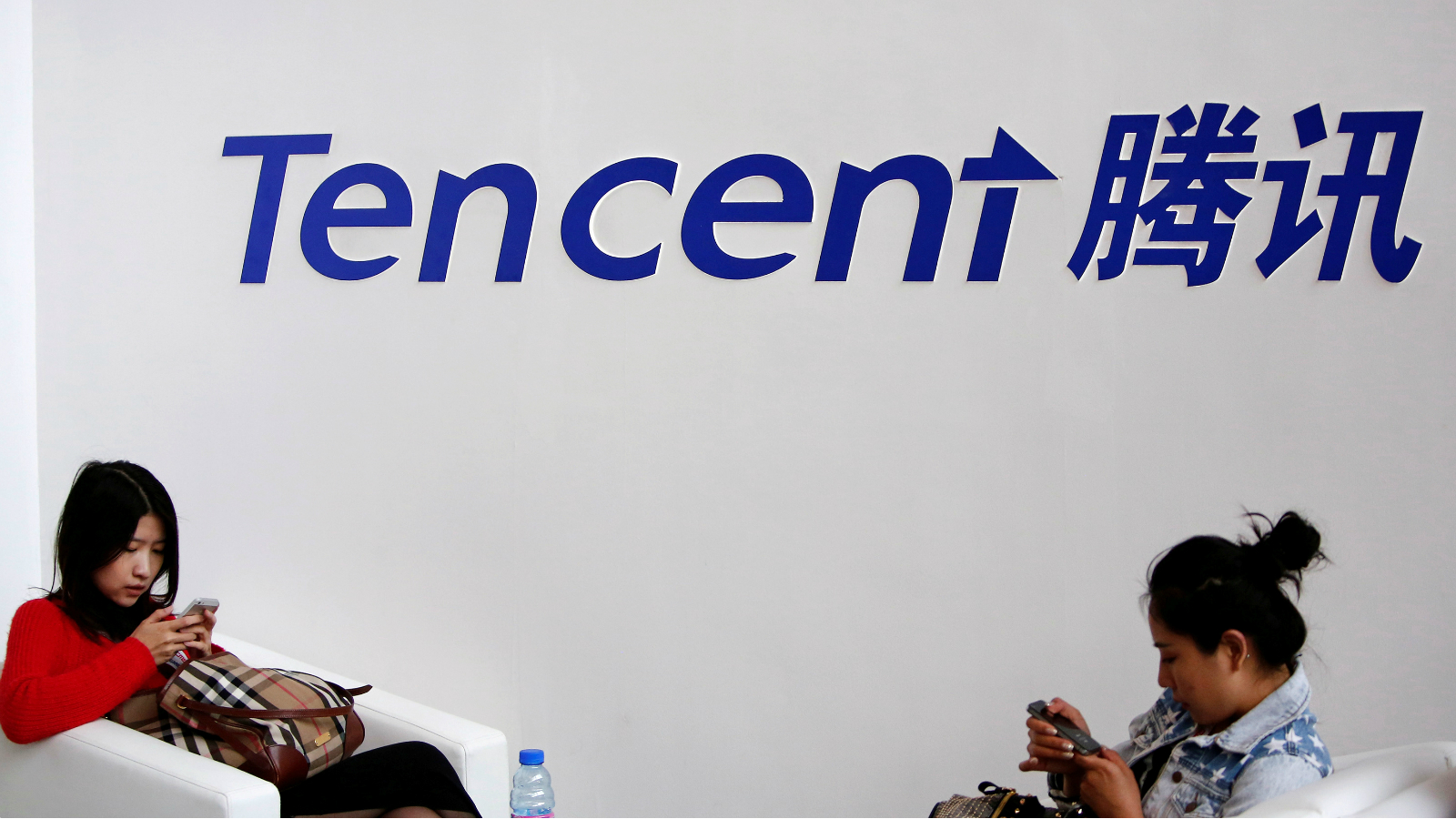 Visitors use their smartphones underneath the logo of Tencent at the Global Mobile Internet Conference in Beijing May 6, 2014.