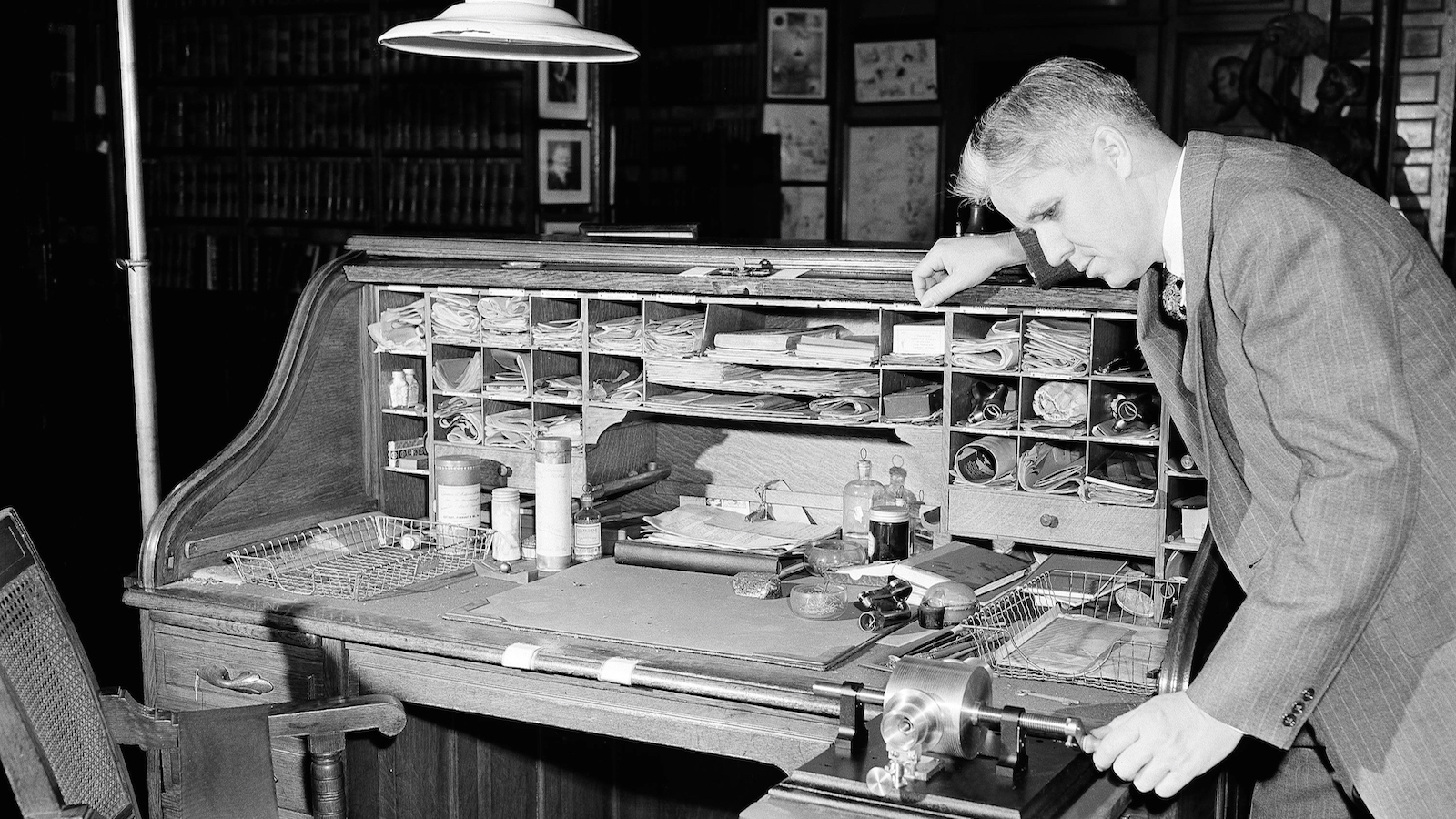 "At the private desk of Thomas A. Edison, Norman R. Speiden, curator of the library on Jan. 27, 1948, studies the inventor's original phonograph, made in 1877. The contents of the desk, as they were found when it was opened in 1946, fifteen years after Edison's death, include a sealed can of lithium, bottle of reduced iron, chlorinated rubber, ""Carissa"" jelly made by a Mrs. Stevens in 1928, old papers and business letters and contract early phonograph, dating from 1878 to 1890. (AP Photo/Carl Nesensohn)"