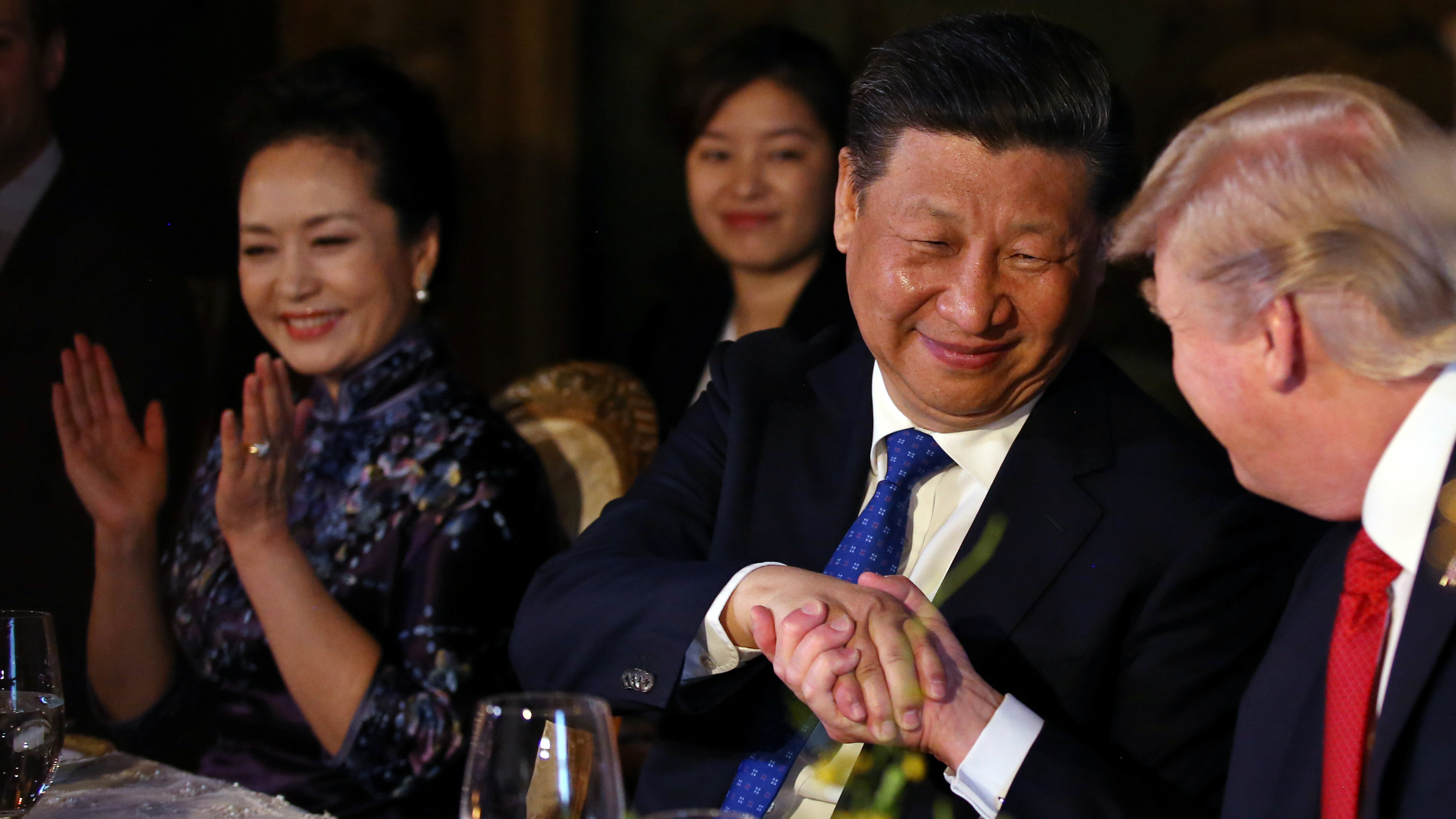 Chinese President Xi Jinping shakes hands with U.S. President Donald Trump as he is accompanied by China's first lady Peng Liyuan (L) during a dinner at the start of a summit between President Trump and President Xi at Trump's Mar-a-Lago estate in West Palm Beach, Florida, U.S., April 6, 2017. REUTERS/Carlos Barria